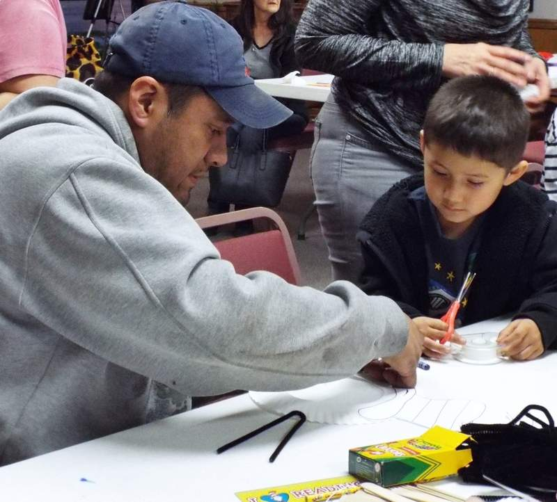 Jacob Zaragoza, 5, of Du Quoin gets some help from dad to finish his be-jeweled cardboard butterfly.