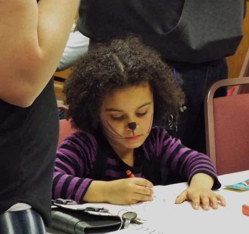 Selena Davison-Fulk, 4, of Du Quoin works on her 'Cat in the Hat' mask.