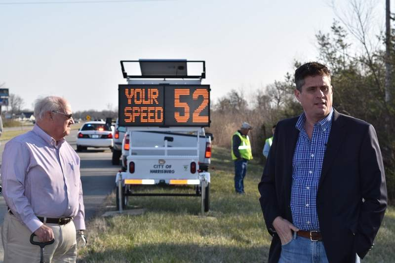 Harrisburg Mayor John McPeek, right, and city insurance adviser Bill Ghent stand alongside the eastbound lane of the Illinois 13 Bypass Thursday morning. Behind them is a portable changeable message sign that monitors speed and relays to a driver how fast he or she is going. The city acquired the device through a grant obtained by Ghent to be used for public safety improvements.