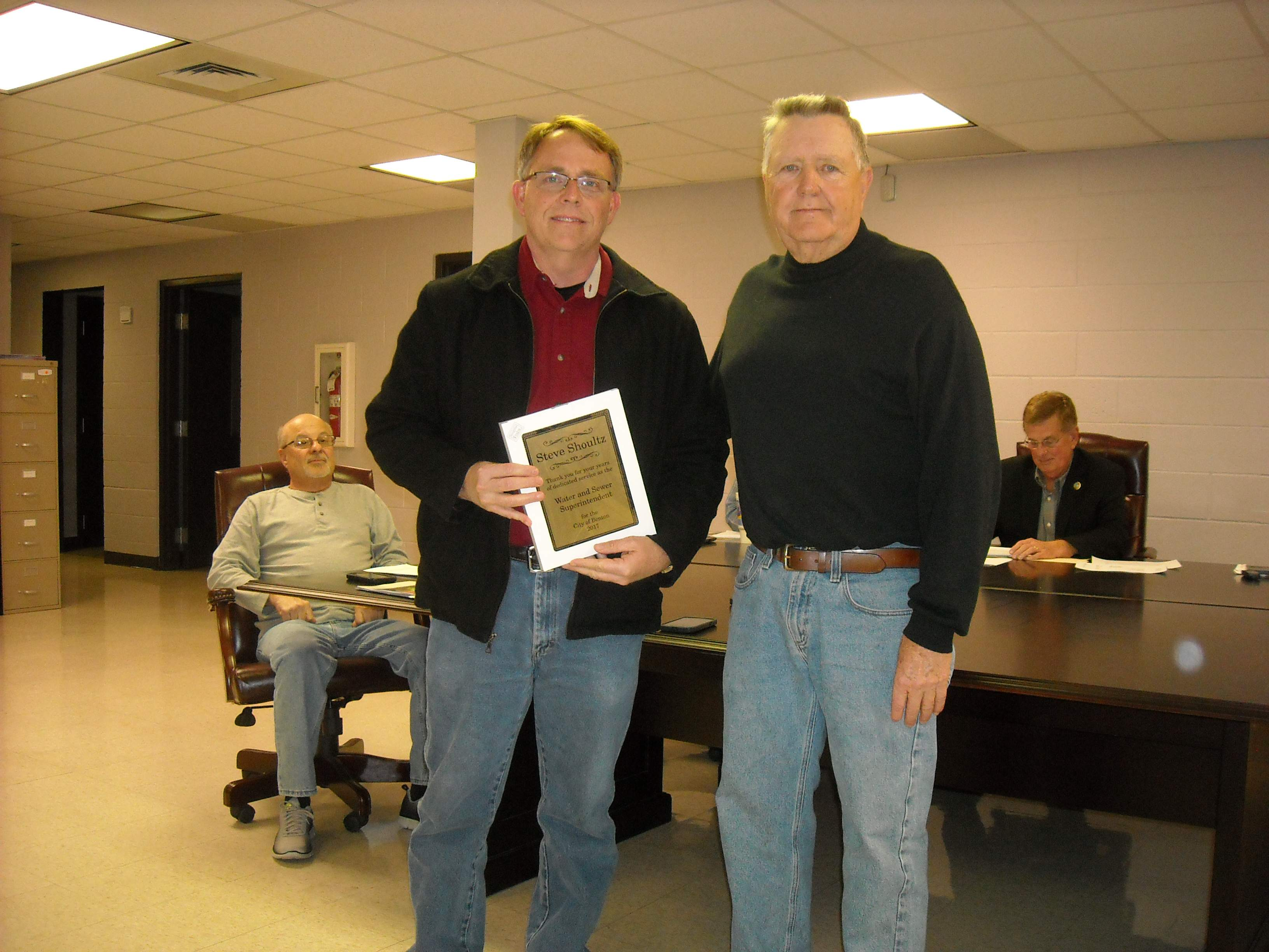 Public Property Commissioner Ronnie Baumgarte, right, presents Steve Shoultz with a plaque for his years of service as the city's water and sewer superintendent. Shoultz's letter of resignation, effective at the end of the month, was read during a city council meeting.
