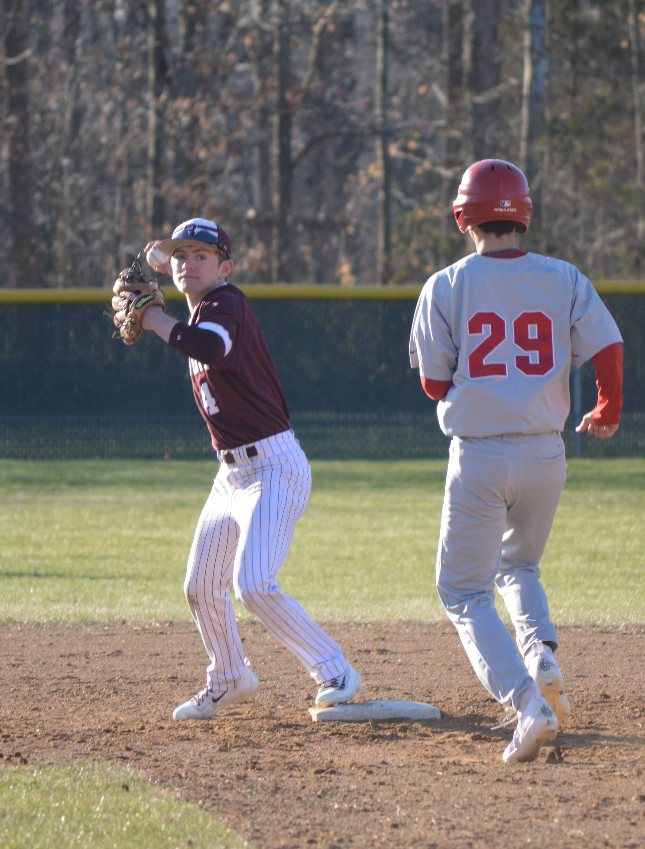 Junior Gehrig Wynn (left) makes an out at second base and looks to throw to first base Wednesday afternoon during the Rangers' home and season opener against the Centralia Orphans at Benton Park.