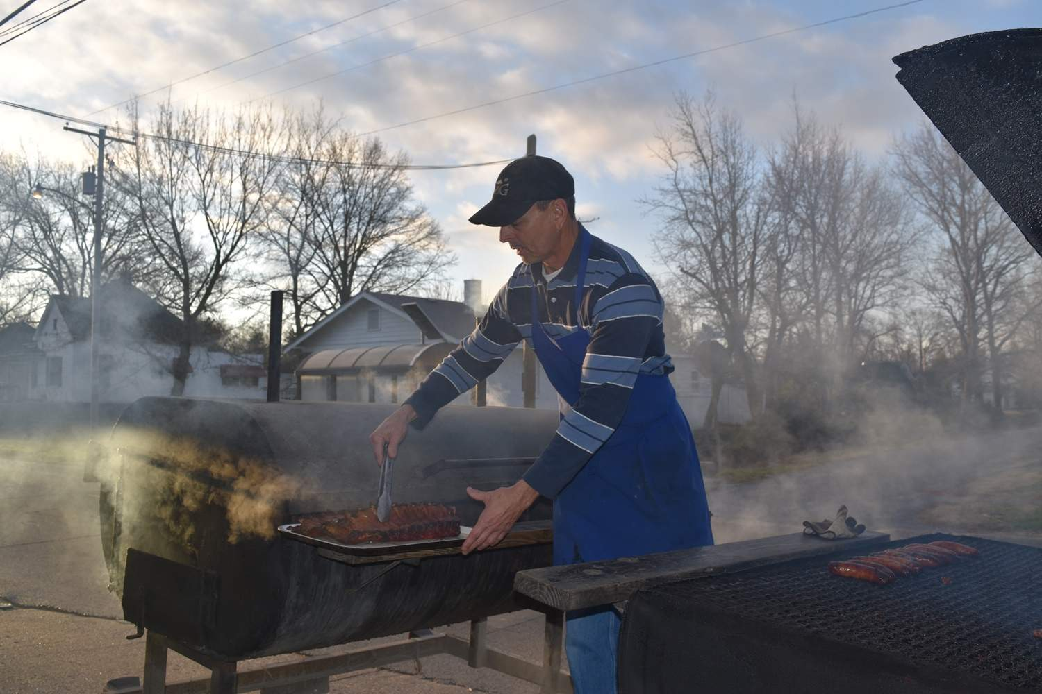 Brett Allen, owner of Sloan Street Market, takes baby back ribs off the grill early Saturday morning.
