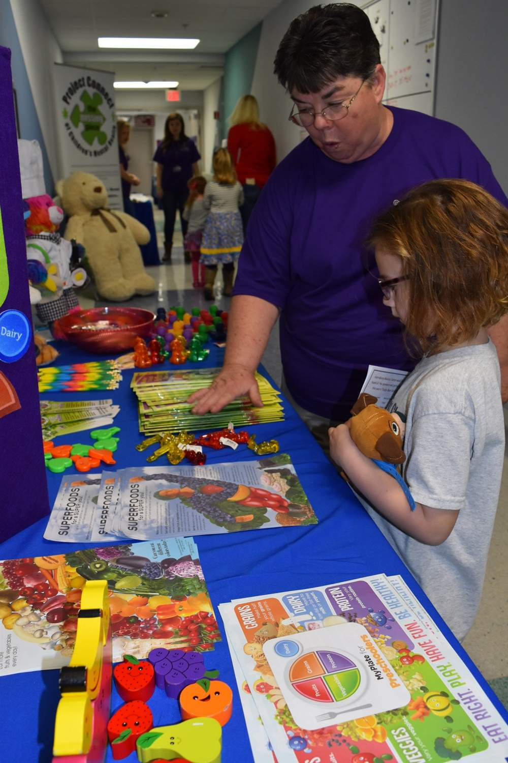 Hallie Hathaway of Marion gets a lesson about safety at a booth at the Teddy Bear Care Fair at Harrisburg Medical Center Saturday.