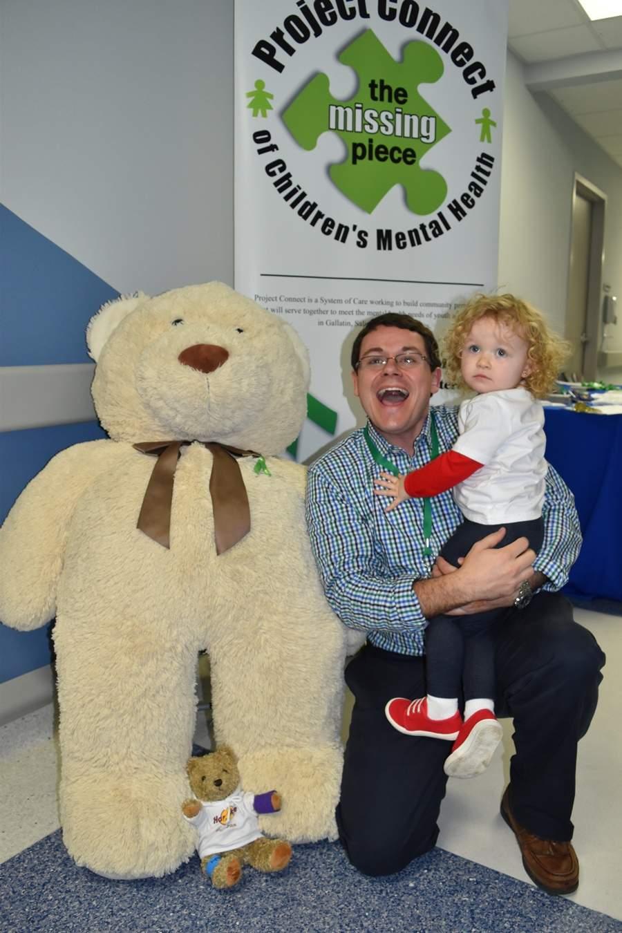 Mattie Buckman of Eldorado sits with her father, Dr. Matt Buckman from Egyptian Health Department, by a giant teddy bear at Harrisburg Medical Center's Teddy Bear Care Fair Saturday at HMC.