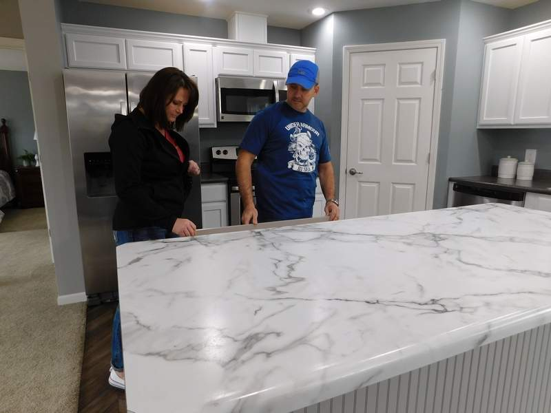 Bridgette Howell and Shawn McClure of Benton inspect the self-closing drawers in the kitchen of a model home at Pine Ridge Homes in Benton. Pine Ridge held an open house last weekend to celebrate its move to Petroff Road in Benton. 'We've been in business in Vandalia for 20 years,' said sales manager Mike Henson. 'We came down here because we are doing something different from everyone else.' Henson said the homes are built in Indiana in 'pieces' and then transported to the customer's building site. 'About  60 percent of the construction is actually done on-site,' Henson said.