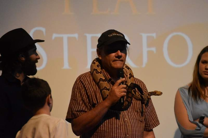 """Tony Gerard, a biologist and animal handler for """"Dig Two Graves,"""" talks to the audience while Sintullo, a large timber rattlesnake featured in the film, drapes across Gerard's shoulders."""