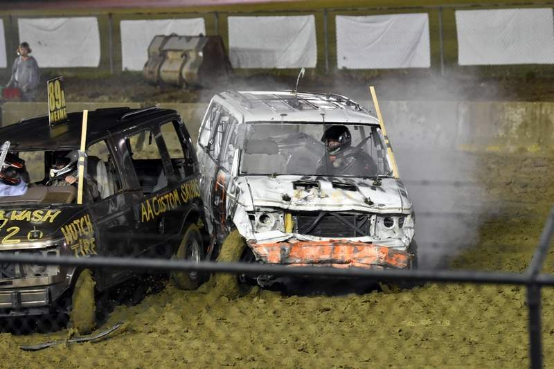 """""""Batman"""" (right) and Alex Heine battle it out in the Minivan Division on Friday, the first time minivans have participated in the Sparta Days Demolition Derby. Heine was the winner."""