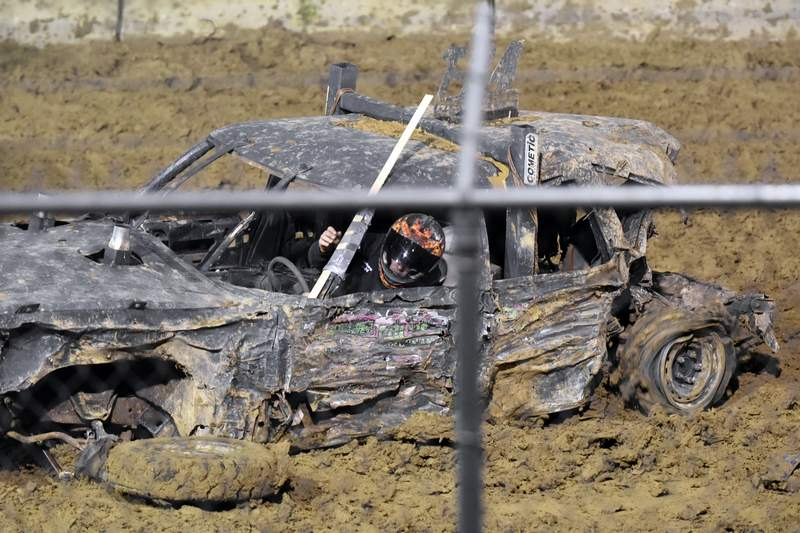 A driver looks down at his front wheel, which had just fallen off during the semi-stock feature event.