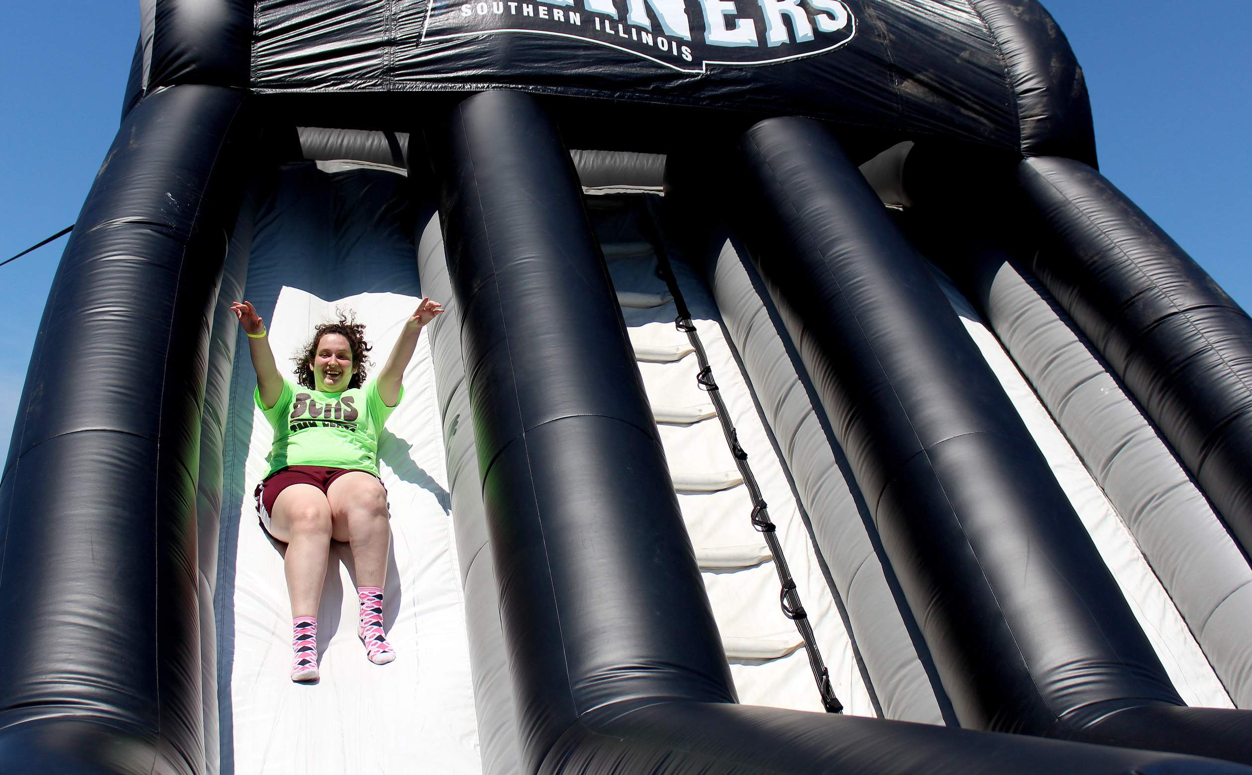 Shawna Melvin, a continuing senior at Benton Community High School, races down the inflatable slide at Rent One Park in Marion Tuesday. Melvin and hundreds of other students from around the area were at the park on Tuesday to take in a Miners exhibition game as part of the park's Education Day.