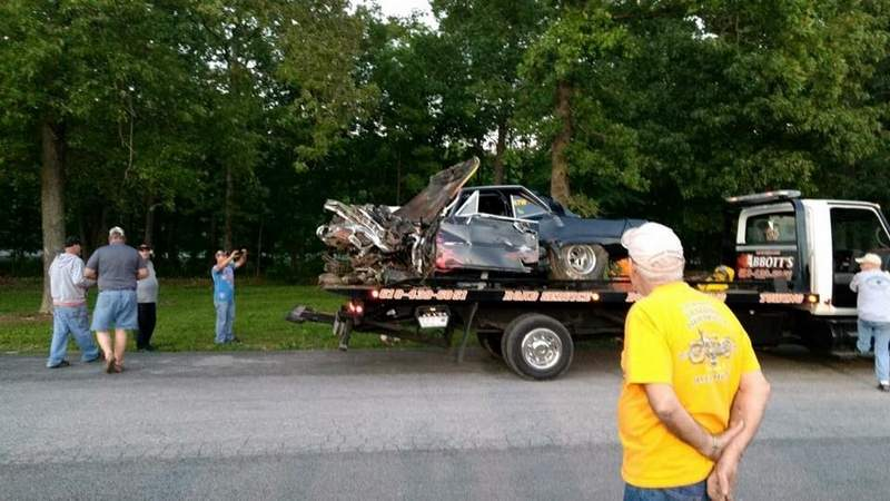 Shown are the vehicle's remains being towed from the scene.