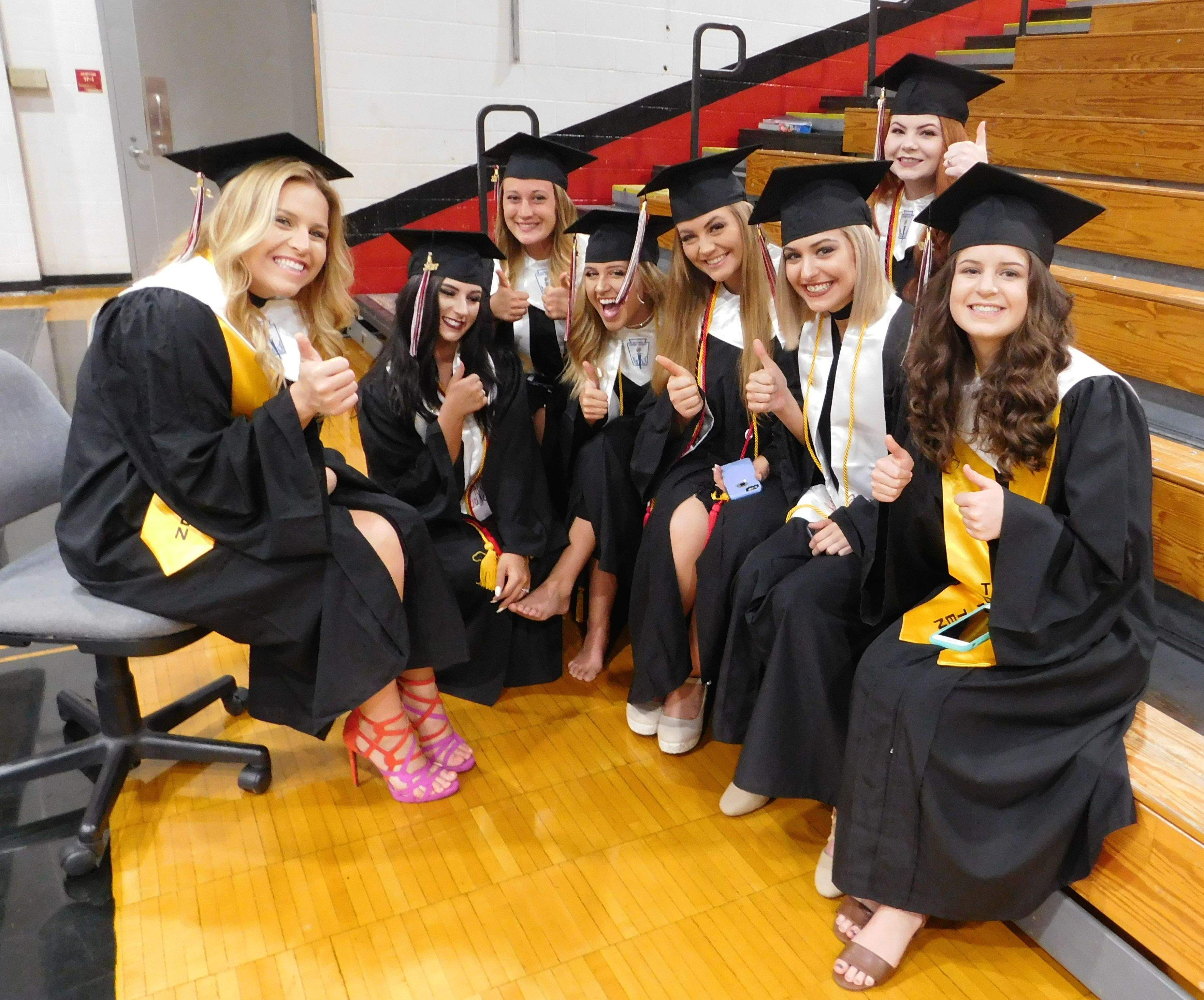 """Maddie Johnson (left) sits with a group of fellow graduates waiting for the ceremony to begin.  The fourth-rank academic standout, Johnson's presence at last night's event was nothing short of a miracle.  She underwent an emergency appendectomy at 11 a.m. yesterday, leaving the hospital just five hours after the surgery was completed.  """"She's one tough kid,"""" wrote her grandmother, Randi Price, on Facebook."""