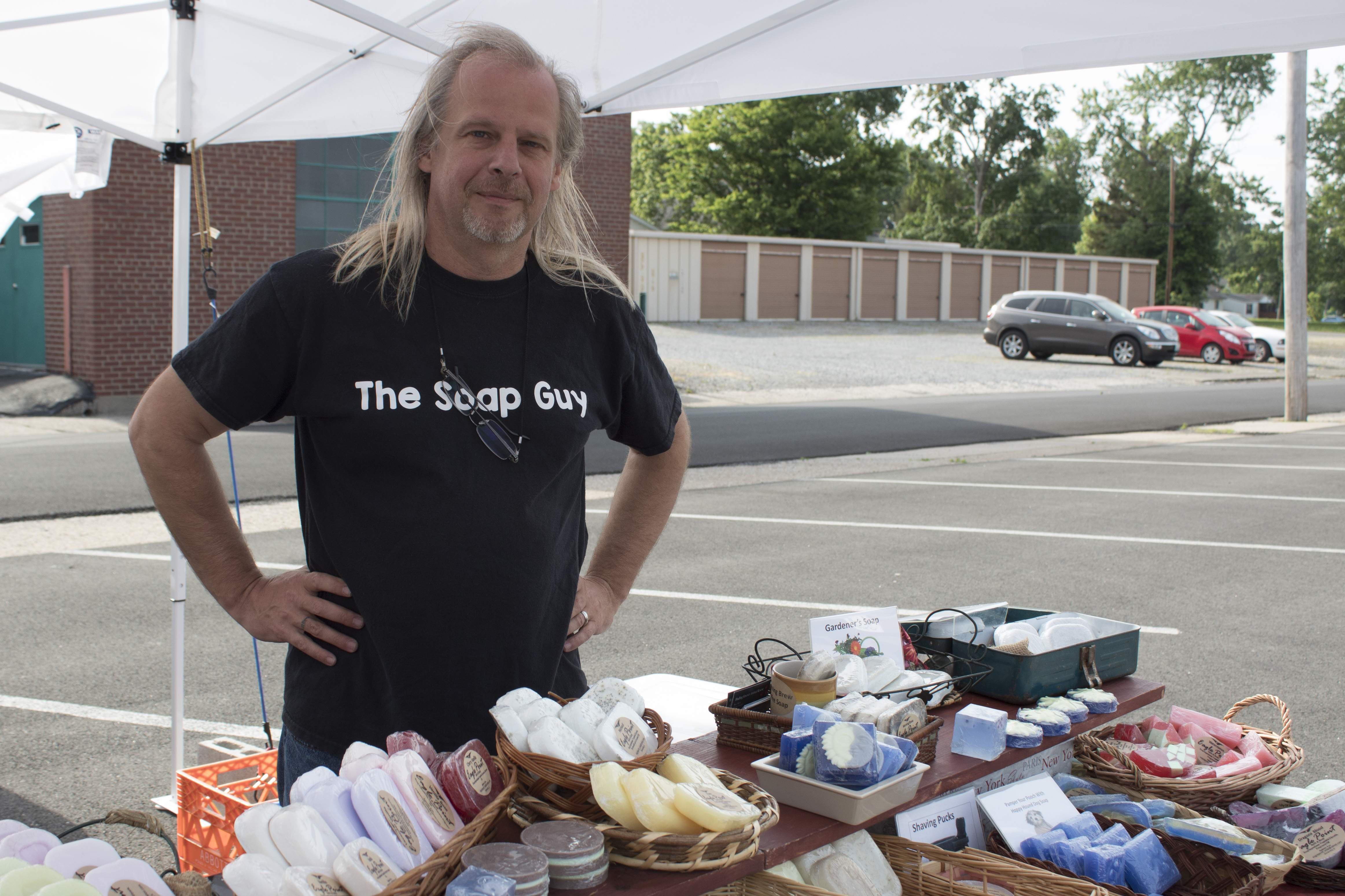 Dan Druszkowski fights the wind Wednesday morning at the Farmer's Market held in the Marion Senior Citizen's Center parking lot. Dan owns Eagle Point Bath and Body in Goreville. Eagle Point offers handmade soap, lotions, salves, and other scented products.