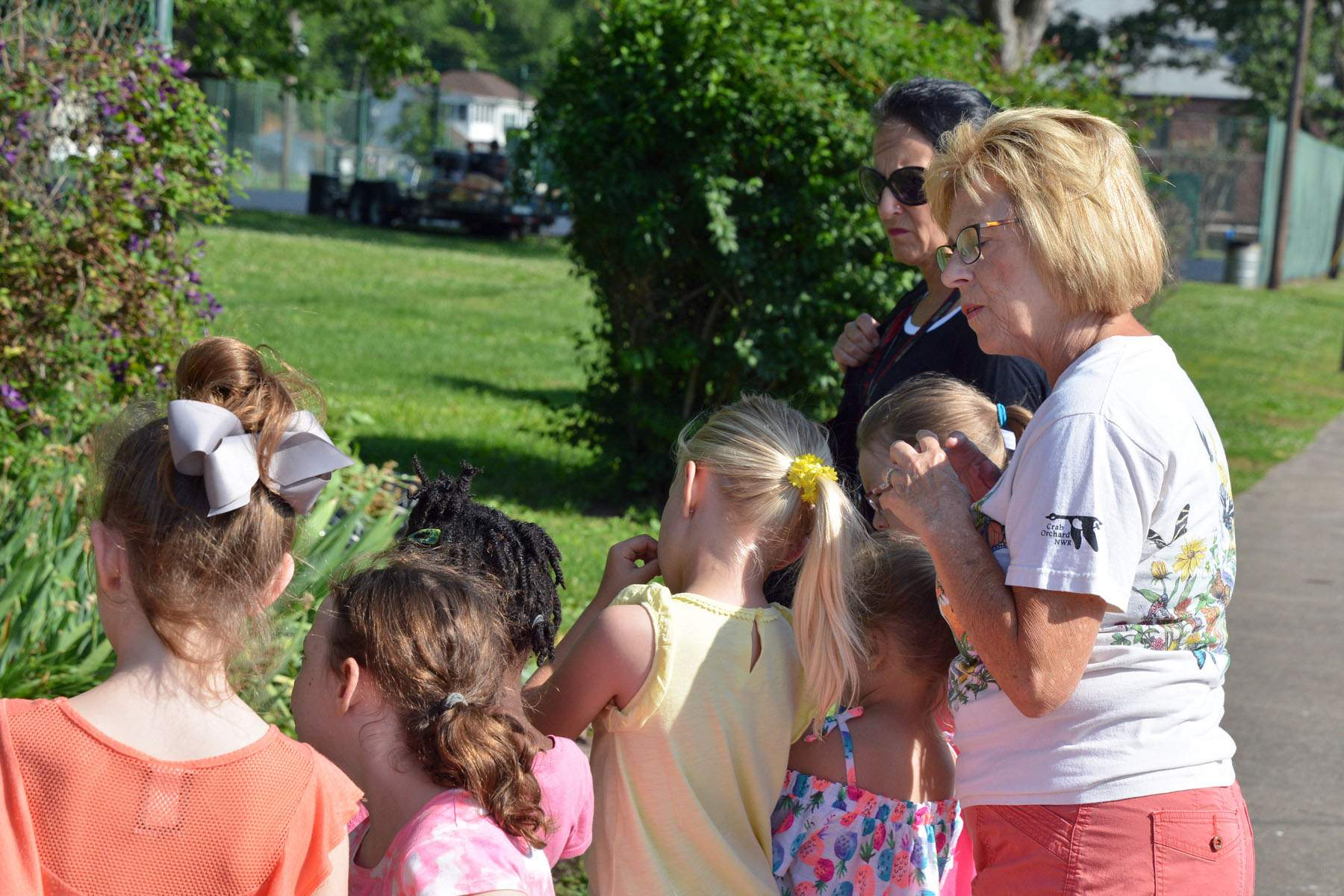 Pictured is first-grade teacher Sandy Stanhouse and several students getting tips on gardening from Garden Club member Joey Harsy.