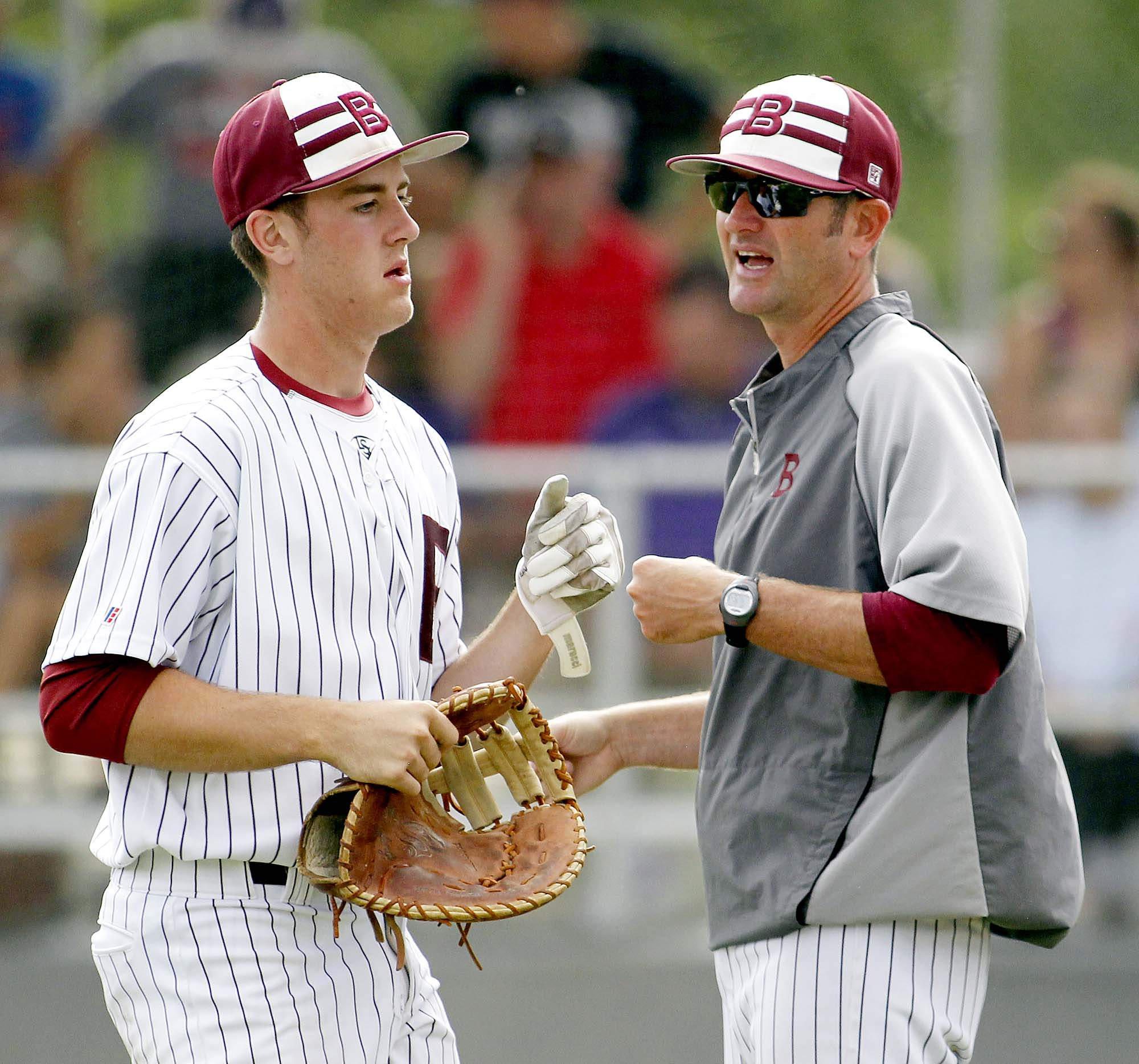Benton head coach Brett Blondi congratulates Parker Williams following the end of the second inning Wednesday during the IHSA Class 2A Regional at Harrisburg. Benton went on to beat Eldorado 11-3.
