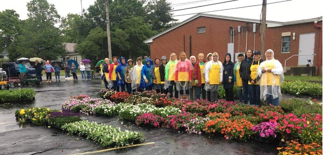 Members of the Eldorado Garden Study Club take a break from the rain to pose with some of their flowers.