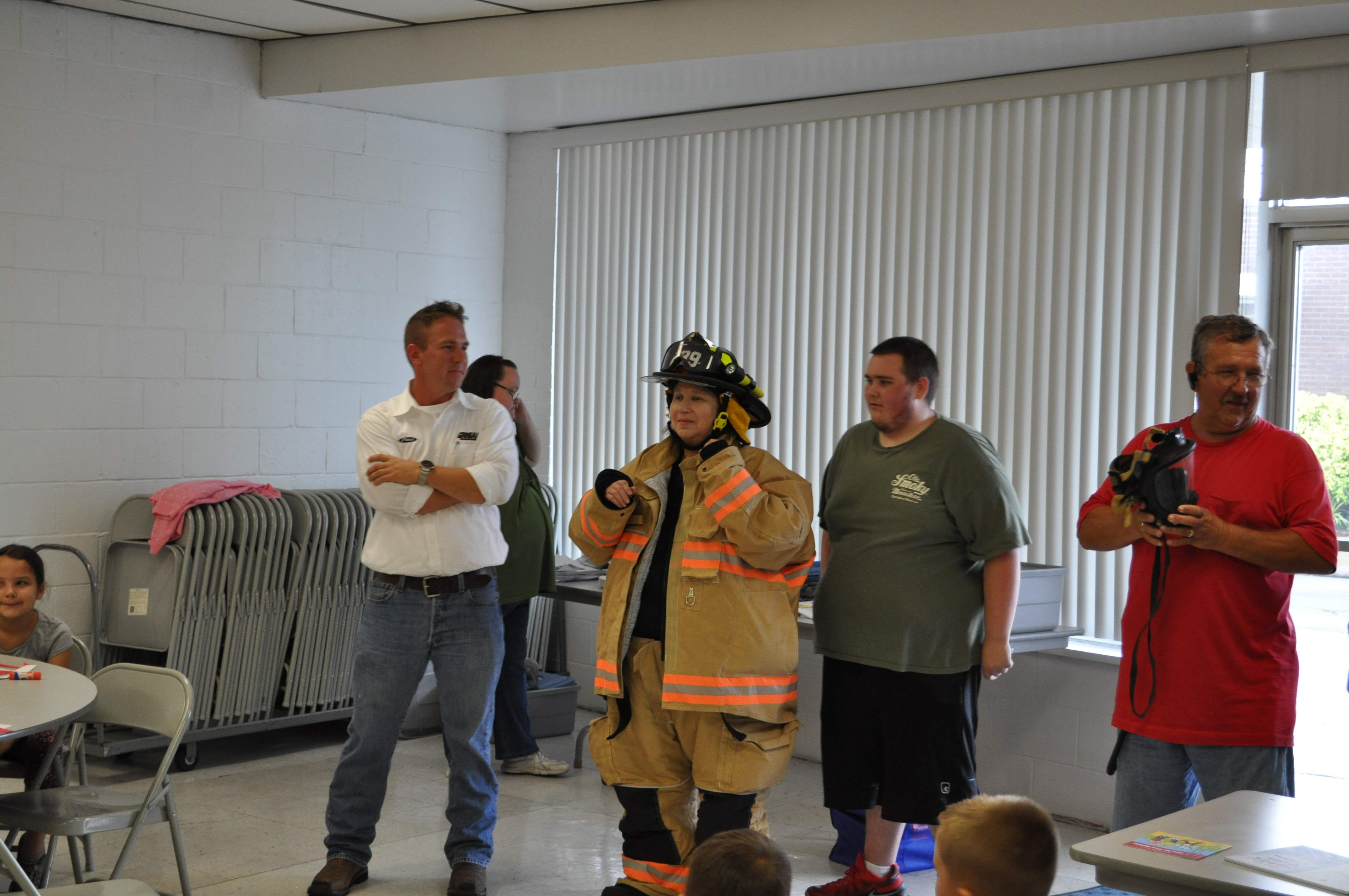 Christopher Library Director Janice Briley dons firefighter gear for the kids at the summer reading program's final session last Thursday. She was assisted by firefighters (left to right) Tim Learned and Josh Estes, as well as Christopher Fire Chief Ron Learned.