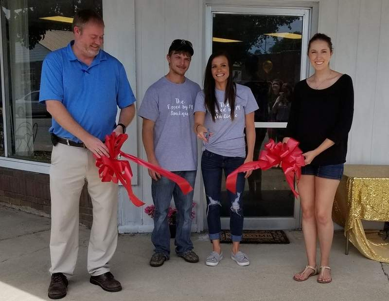 Sesser mayor Jason Ashmore (left) joined new store owners Jacob and Megan Witges, and Chelsea Zettler of Chelsea Rae Photography for the ribbon cutting ceremony of Flipped by M Boutique Saturday. The store carries women's fashions in sizes small through plus.
