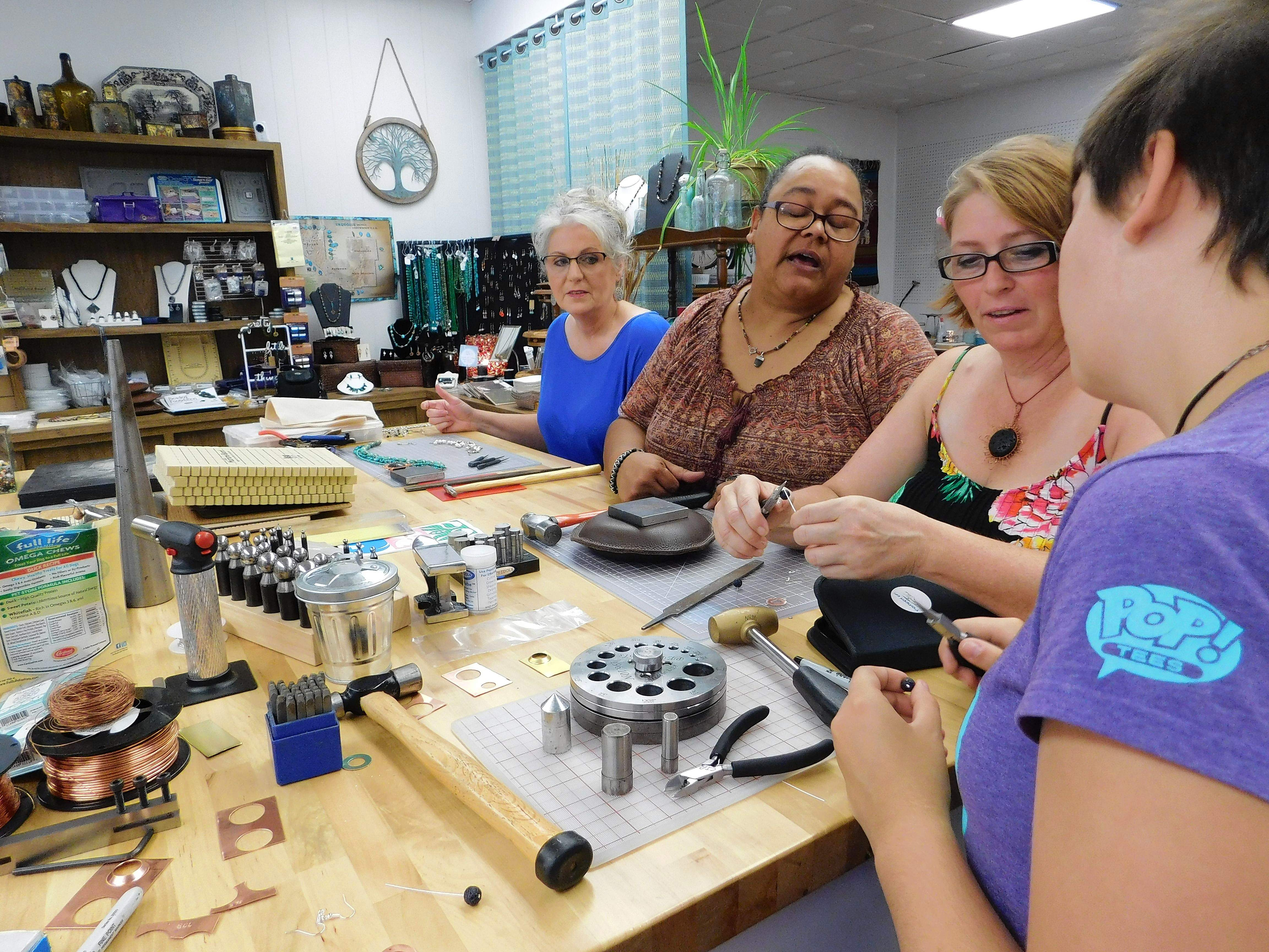 "Nicole Roundtree-Mileur, center, advises Heather Parr and Chloe Parr with their eclipse earrings at Saturday's jewelry making class. Sharon Mausey, behind, said she likes making wearable jewelry. ""This is my second class,"" she said."