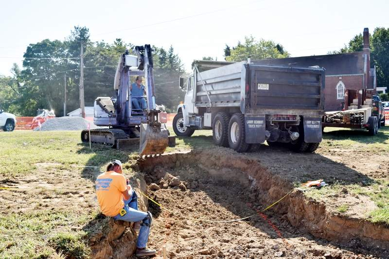 Workers with Red Dot Construction begin digging out the sidewalks on Wednesday for the new memorial park that will honor fallen Chester police officer and volunteer firefighter James Brockmeyer.