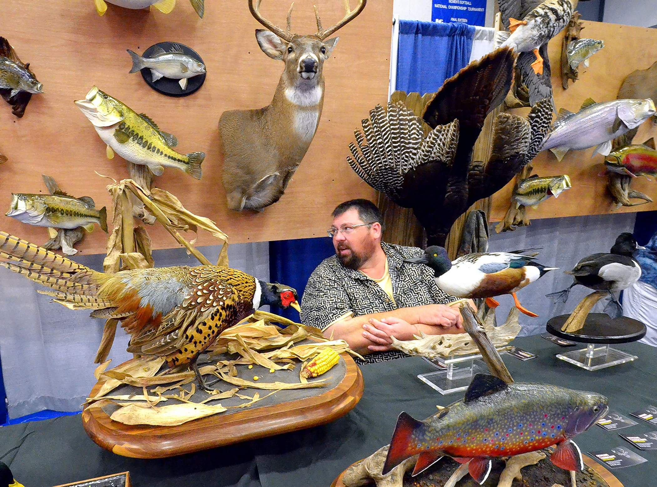 Ewing taxidermist Bryan McGill is surrounded by some of his work at the recent Southern Illinois Hunting and Fishing Days show in Carterville.
