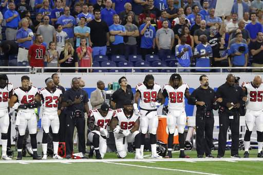 Atlanta Falcons defensive tackles Grady Jarrett (97) and Dontari Poe (92) take a knee during the national anthem before the game in Detroit last Sunday.
