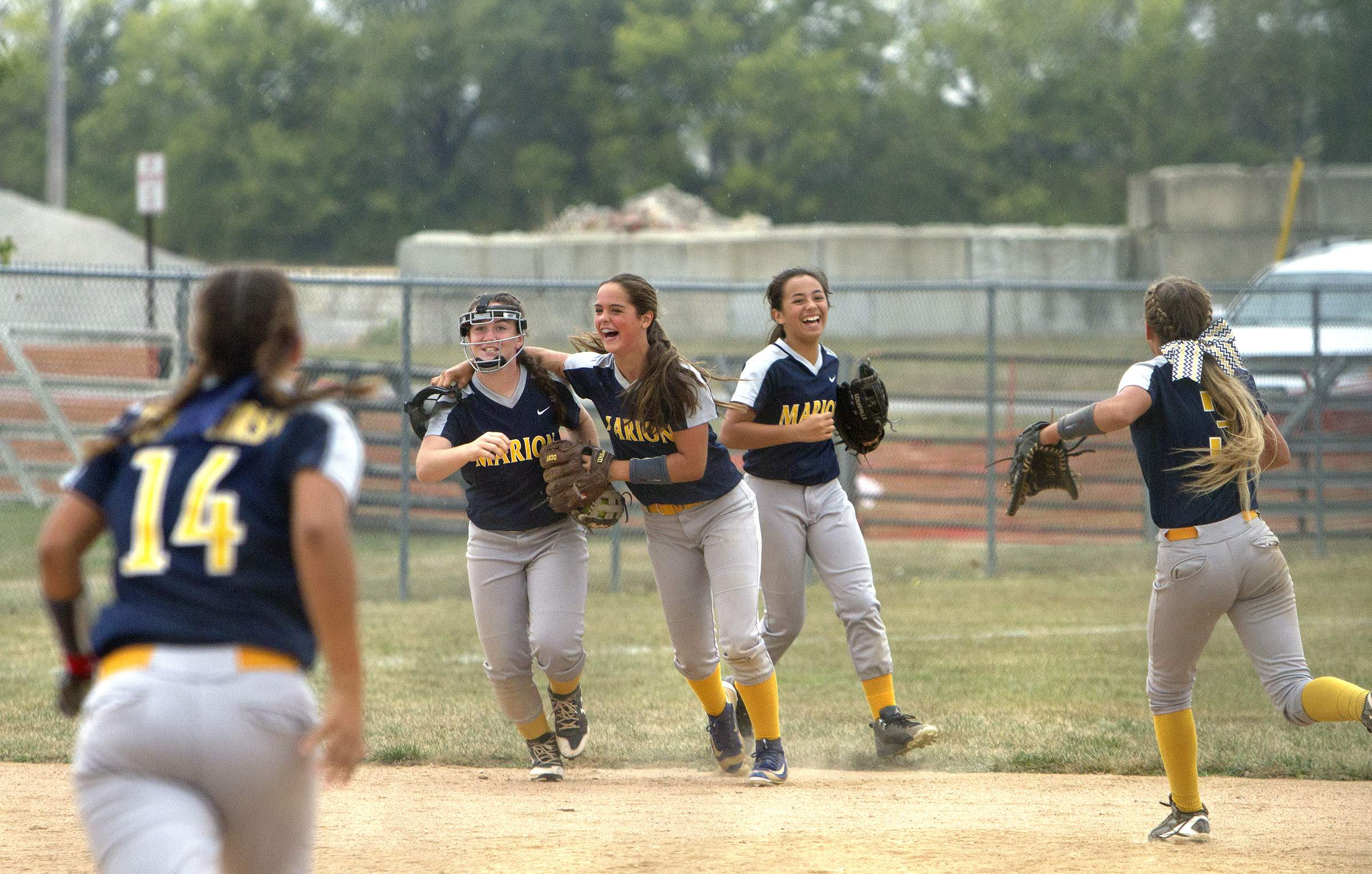 Marion's players celebrate after Amelia Browning (wearing mask) makes a catch for the last out of Tuesday's game.