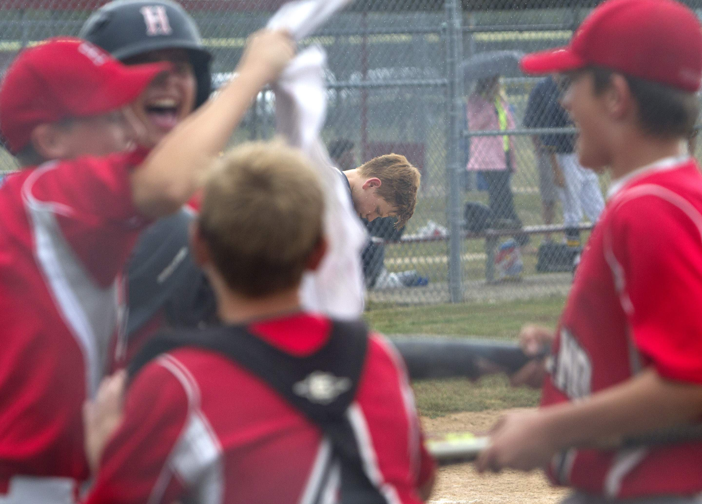 Marion catcher Lukas Shrum looks at home plate in the rain after Highland scored to take the lead Tuesday.
