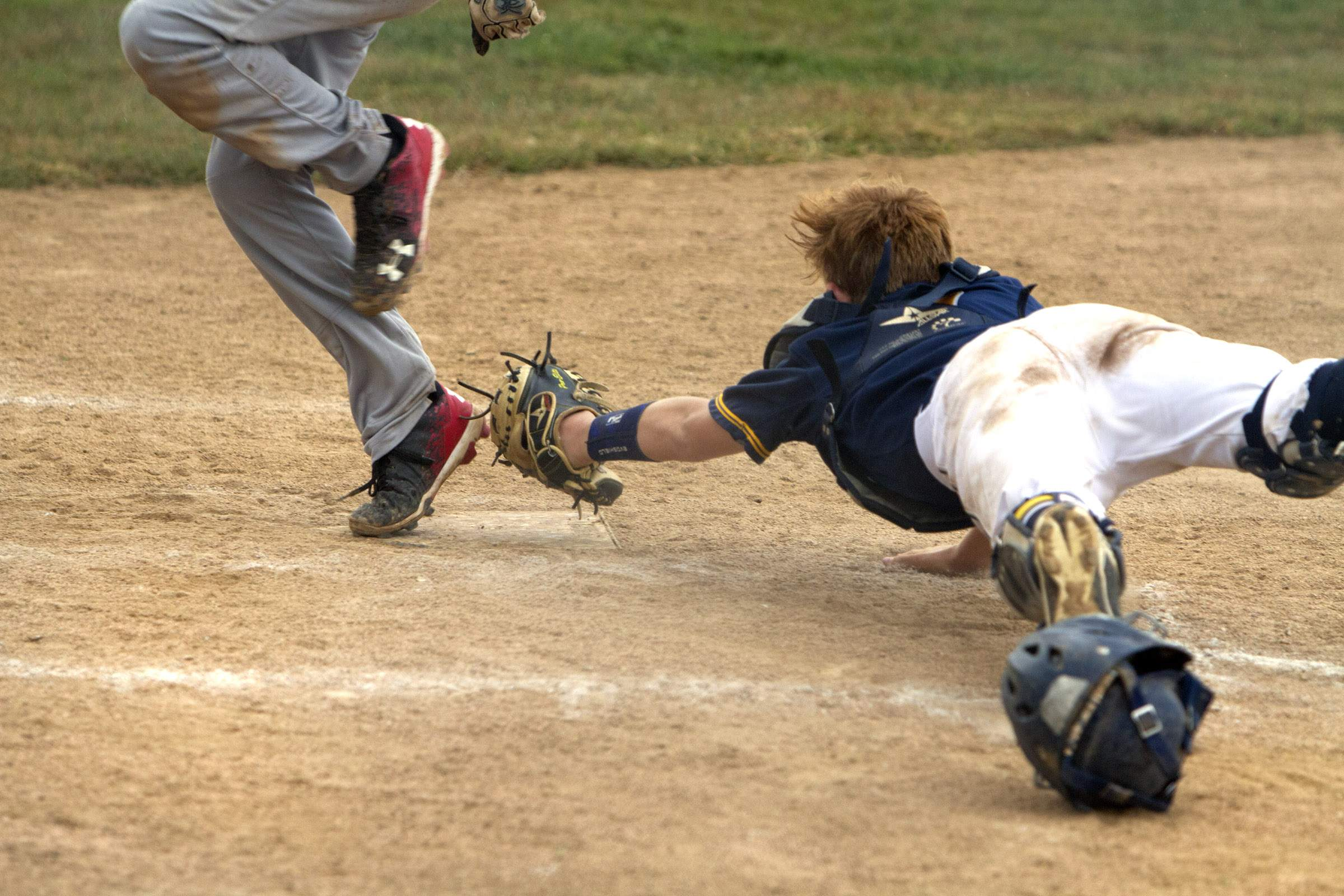 Lukas Shrum tries to tag a runner, but a foul ball was ruled so the run didn't count.