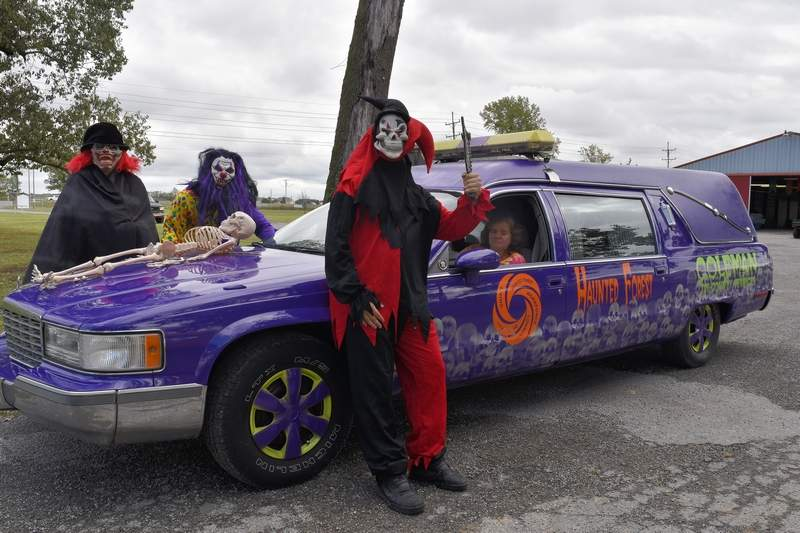 Volunteers for the Coleman Tri-County Services Haunted Forest, from left, Wayman Winters, Bryant Bennett, Ryan Swallow and Haunted Forest director Lisa Knight pause for a moment by the Haunted Forest's new hearse.