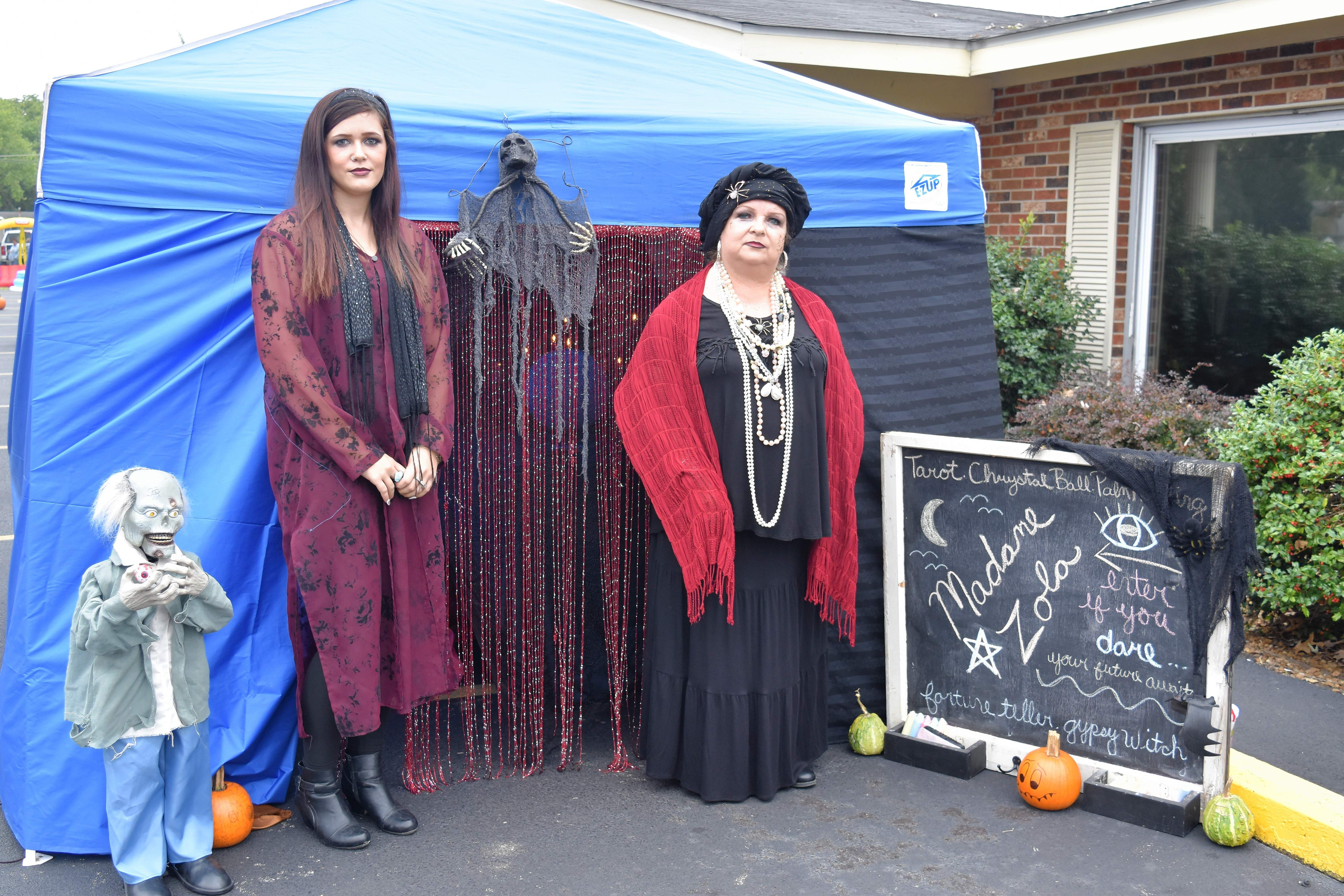 """Madam Zola"" right, portrayed by Glenda Weirauch, and Krysta Nolen run the fortune-telling booth at the Saline Care Center's Fall Festival Thursday in Harrisburg."