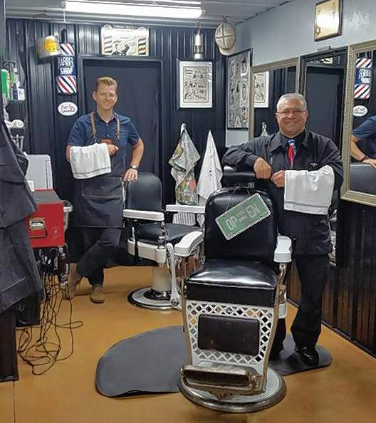 The Armed Barbers pose in front of their vintage barber chairs. John D. Sweet, left, and Ray Minor, right, sought to create not only a great place to get a haircut and shave, but also an atmosphere reminiscent of all the cultural institution that the local barber shop once represented.