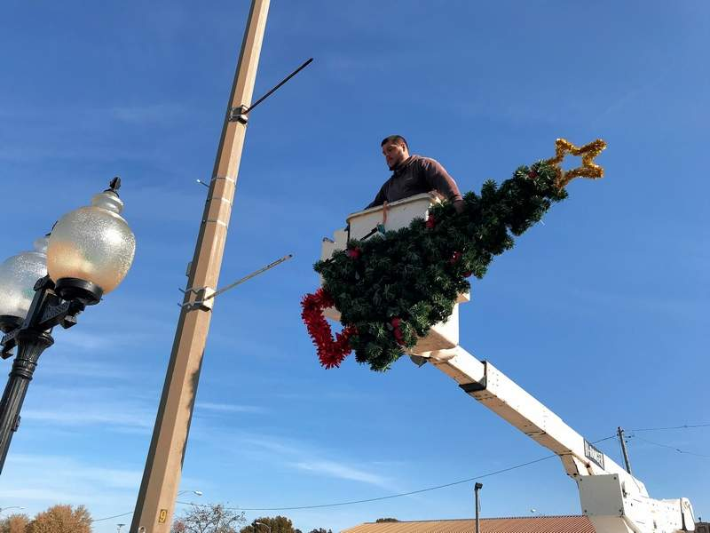 Du Quoin Water Department employee Kyle Jones prepares to place one of the city's new Christmas decorations on Main Street last week.