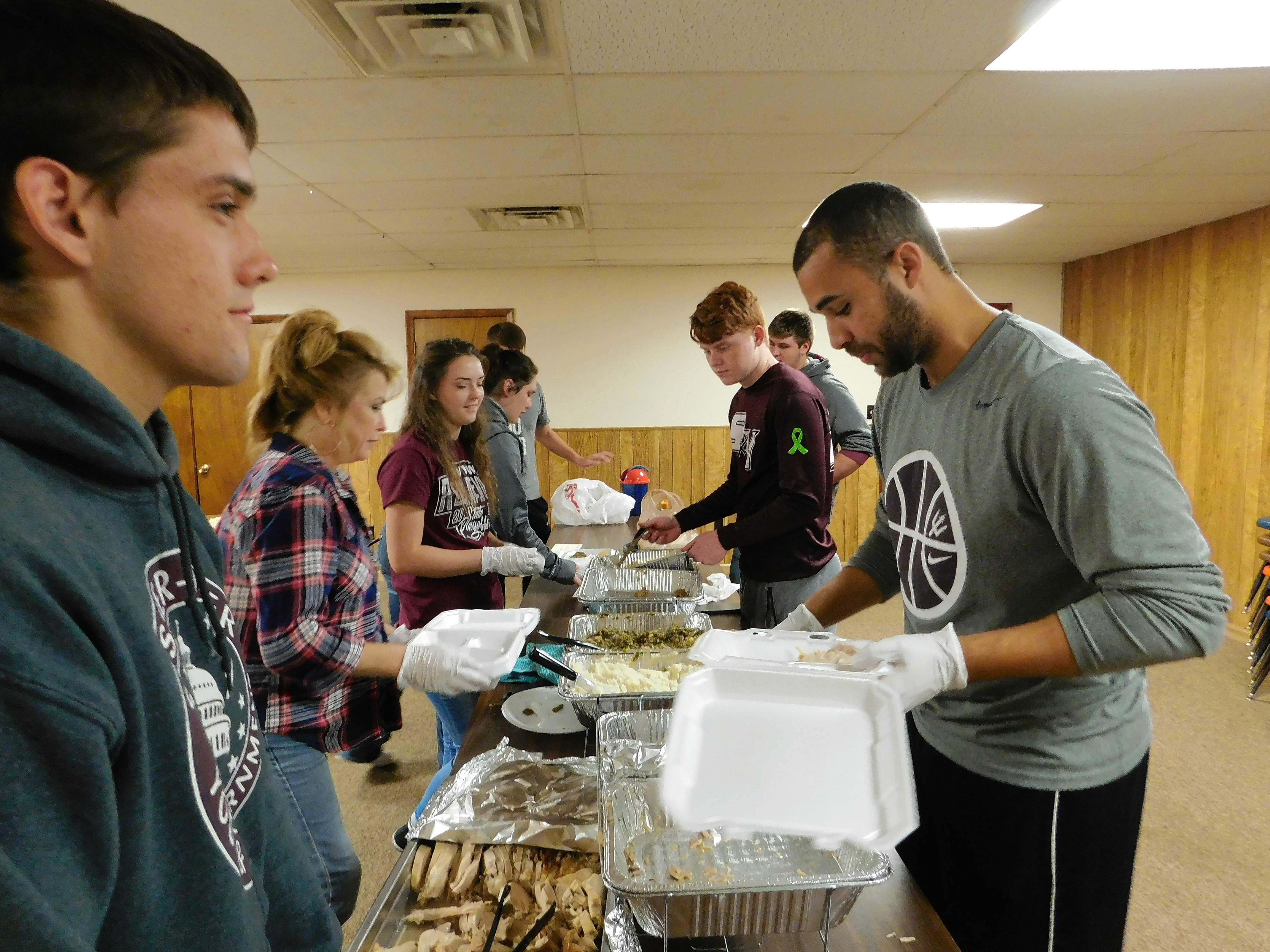 """Volunteers from the Sesser Youth Program help to prepare meals for delivery during last week's Thanksgiving dinner at 5 Loaves Café. """"They are a huge help,"""" said Ashley Boker, one of the organizers of the event."""