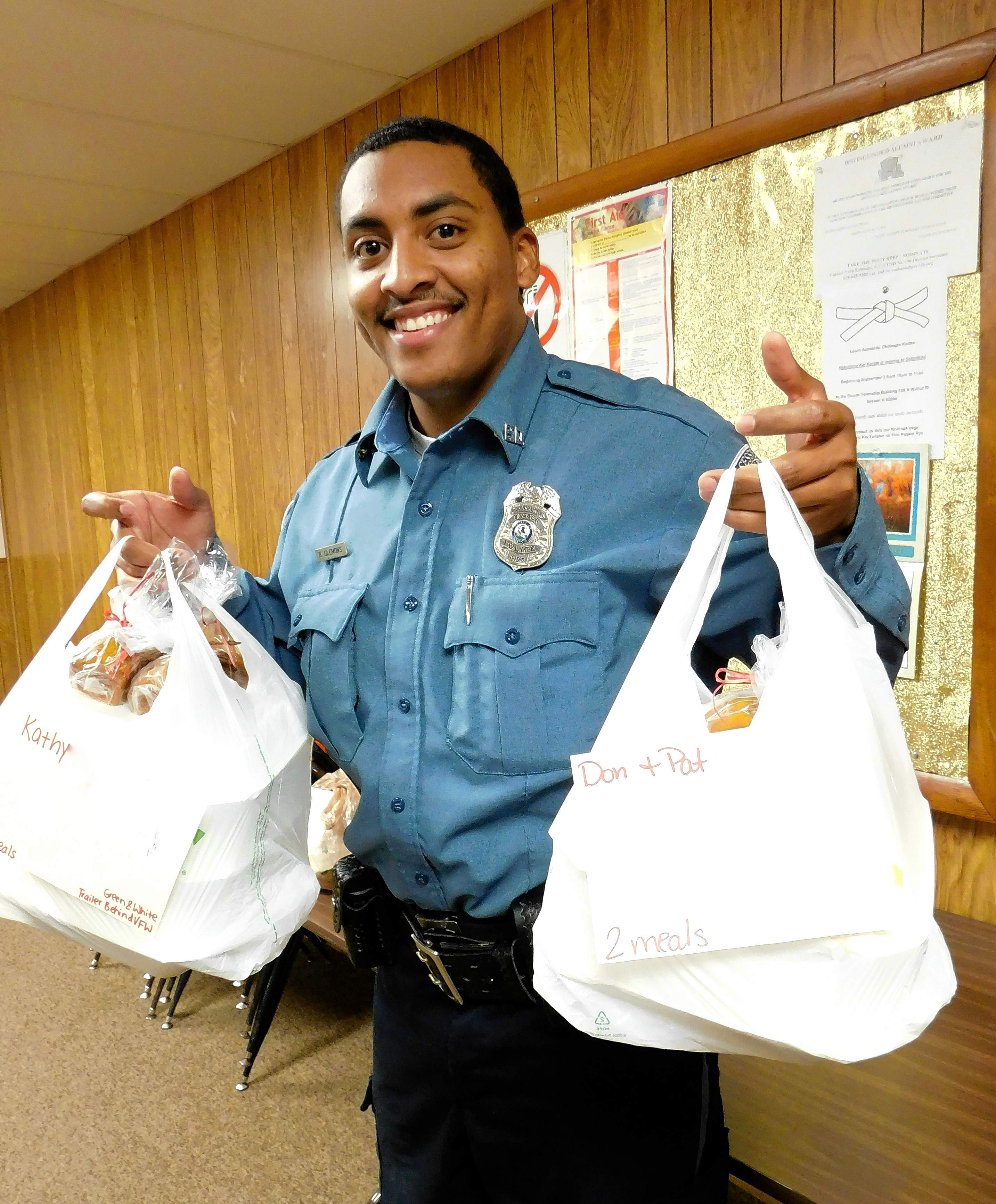 """Sesser police officer Richard Clemons loads up with meals to deliver to those who can't get out.  """"I love giving back to my community,"""" he said."""