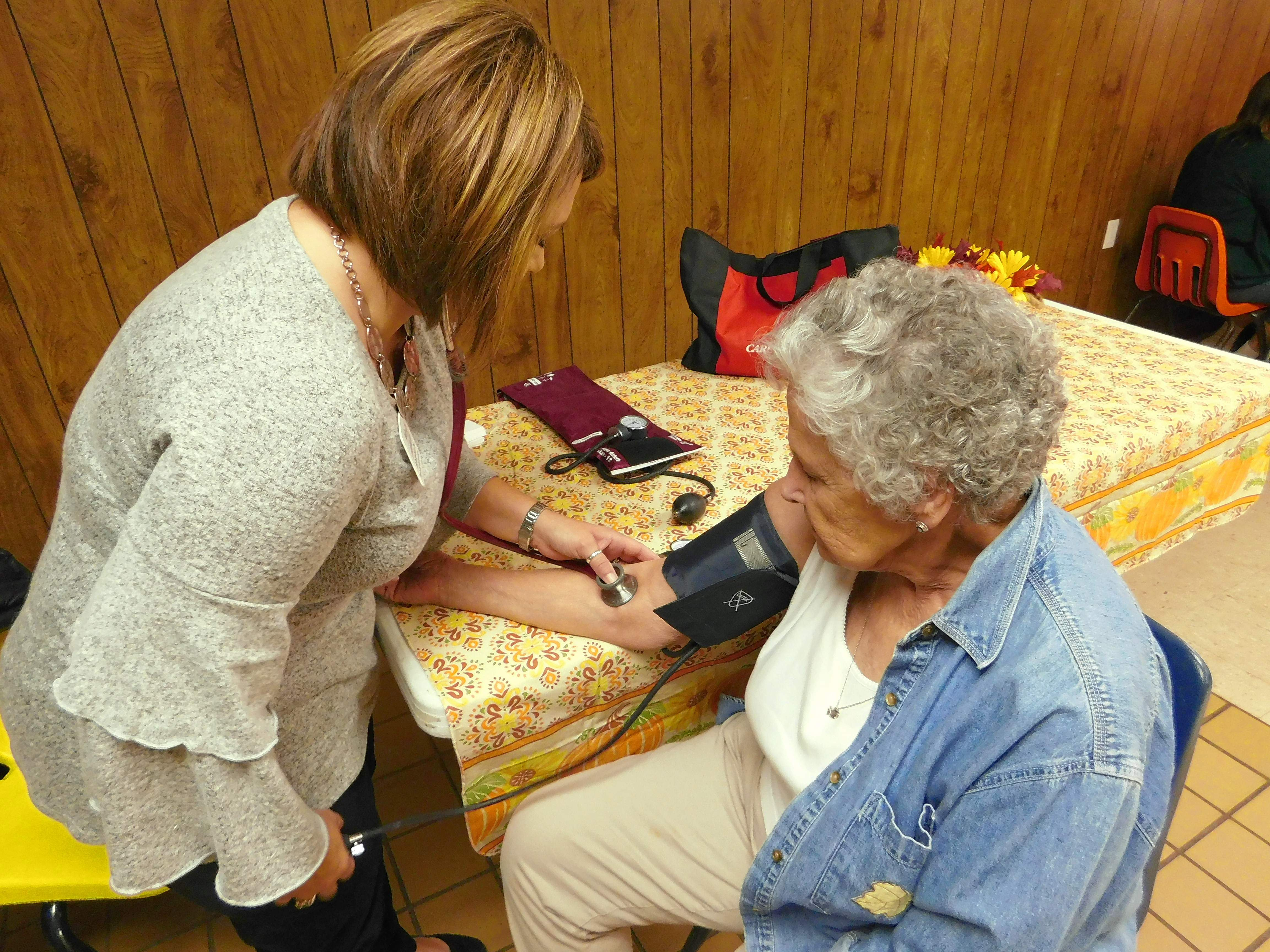Registered nurse Michelle Rollins, left, does a blood pressure check for Phyllis Pearson. Rollins said she saw a need she could fill, adding another valuable service to the community dinner.