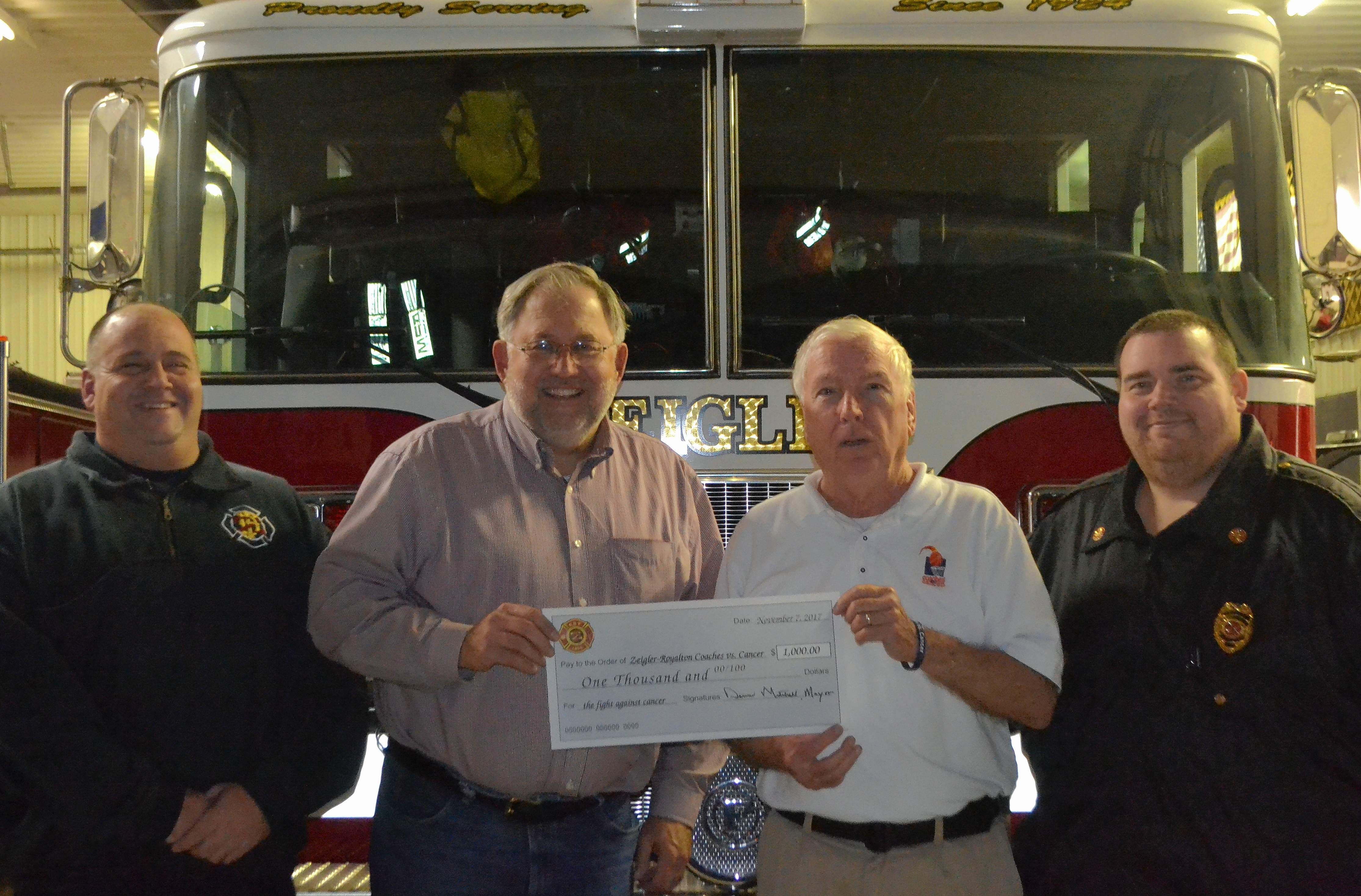 Zeigler Fire Department assistant chief Ronnie Diuguid, Zeigler Mayor Dennis Mitchell and Zeigler Fire Chief Ryan Buckingham present a check for $1,000 to Randall Risley, Zeigler-Royalton Coaches vs. Cancer representative.