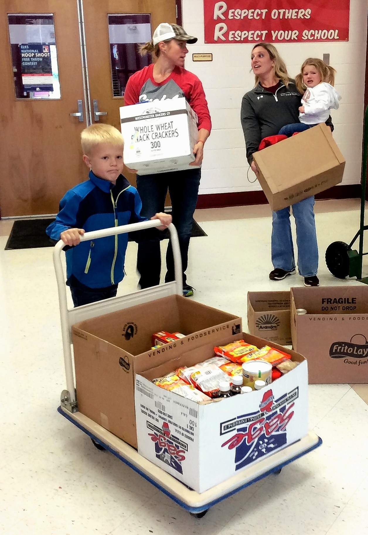 The parade of supplies is led by first grader Cade Pollastro, with a cartload of food. Following behind are moms Nykelle Pollastro and Kortni Blondi (with Ada Blondi in tow).