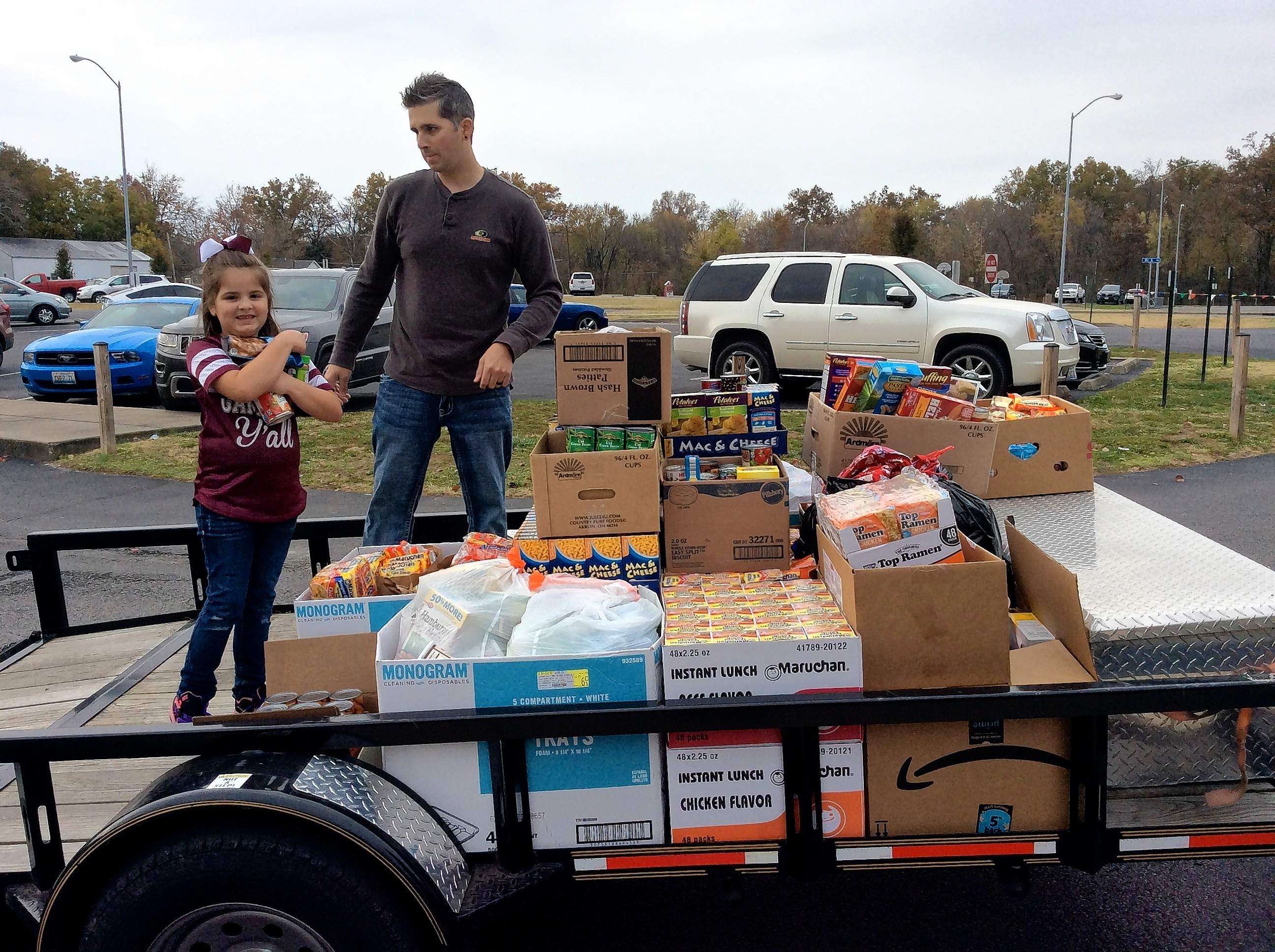 James Neff and his daughter, Shailey, load a trailer of food and clothing in the Benton Grade School parking lot.