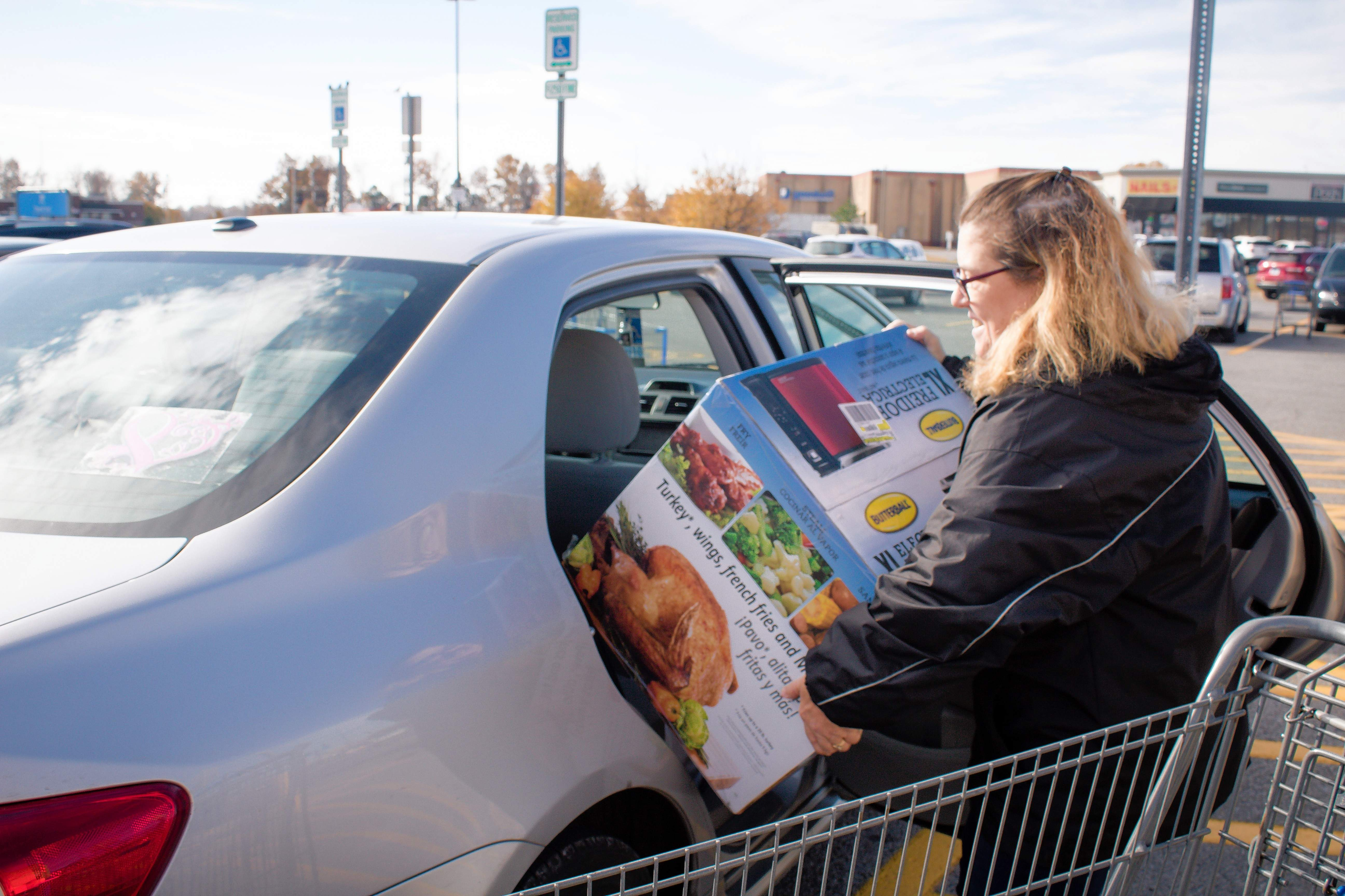Kathy Akes of Marion loads up her car after Black Friday shopping at Marion Walmart.