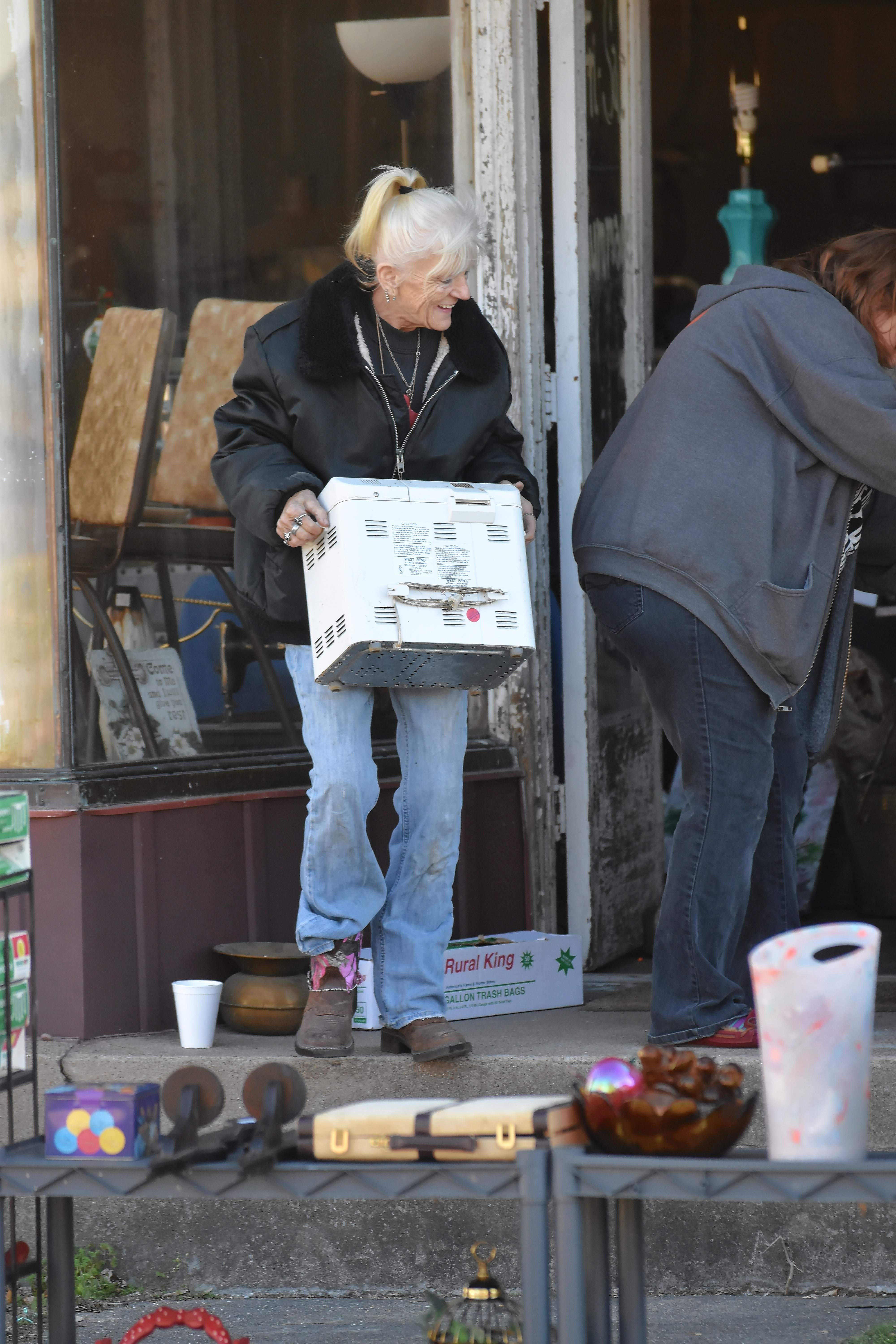 Sandy Gwaltney of Eldorado moves a box as she sets up for the reopening of her business, Cassandra's Forget Me Not ... Again. Gwaltney's old store burned on Oct. 29.