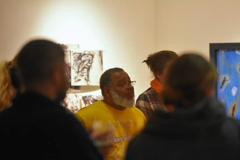 Surrounded by SIUC and SIC art students, SIUC art professor Najjar Abdul-Musawwir discusses abstraction techniques used in the SIC art gallery display of his students' works Thursday evening. Abdul-Musawwir curated the show, which features the work of SIUC Celine A. Chu Scholarship contest. The show will be on display 8:30 a.m. to 4:30 p.m. Monday through Friday and during special events at the college's George T. Dennis Visual and Performing Arts Center until Jan. 8.