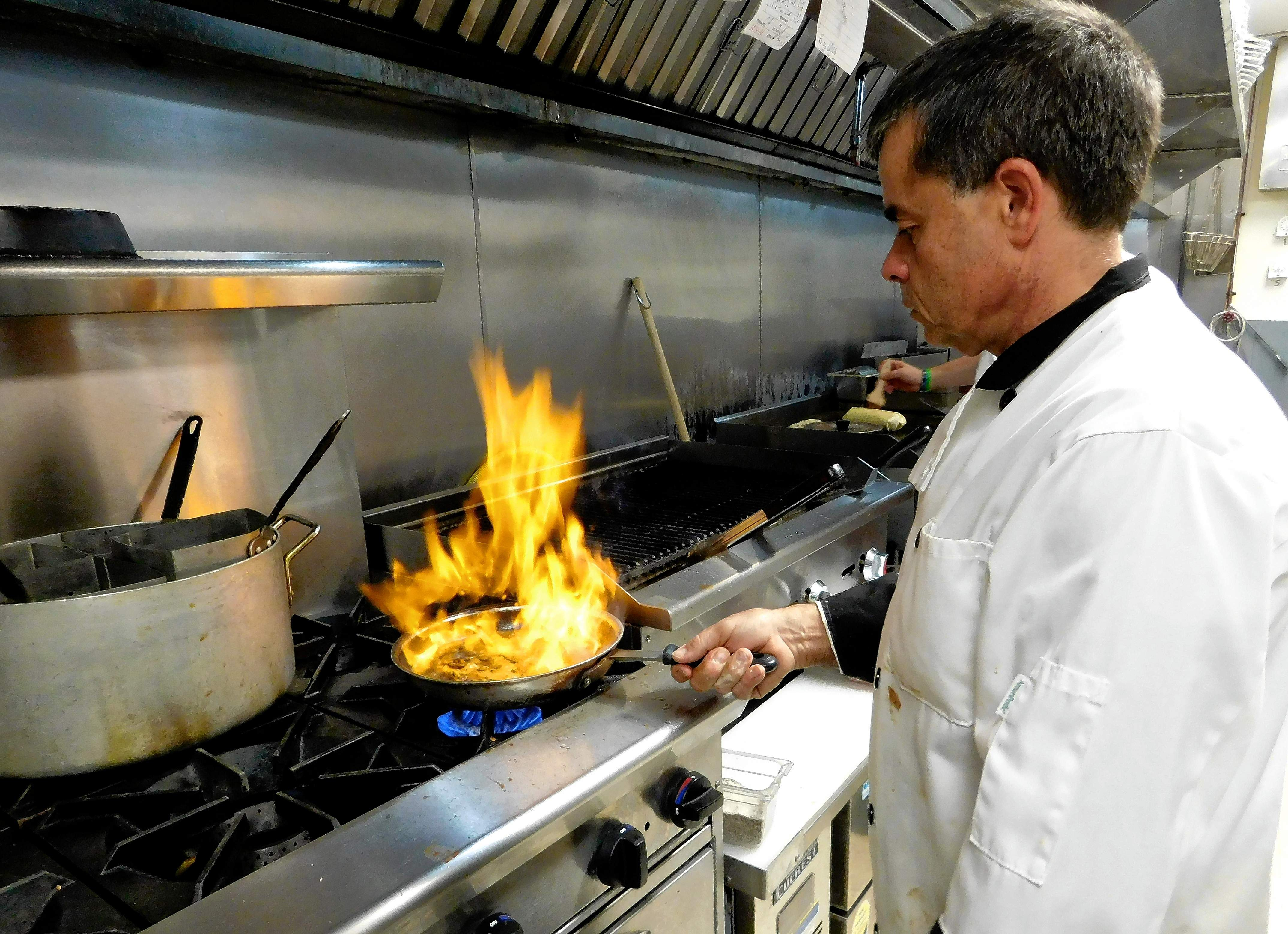 "Michael's Ristorante owner Mike Intravaia prepares a ""flaming dish"" during Tuesday's popular wing night.  Intravaia was able to reopen this week after a July 7 electrical fire caused major damage to the restaurant."