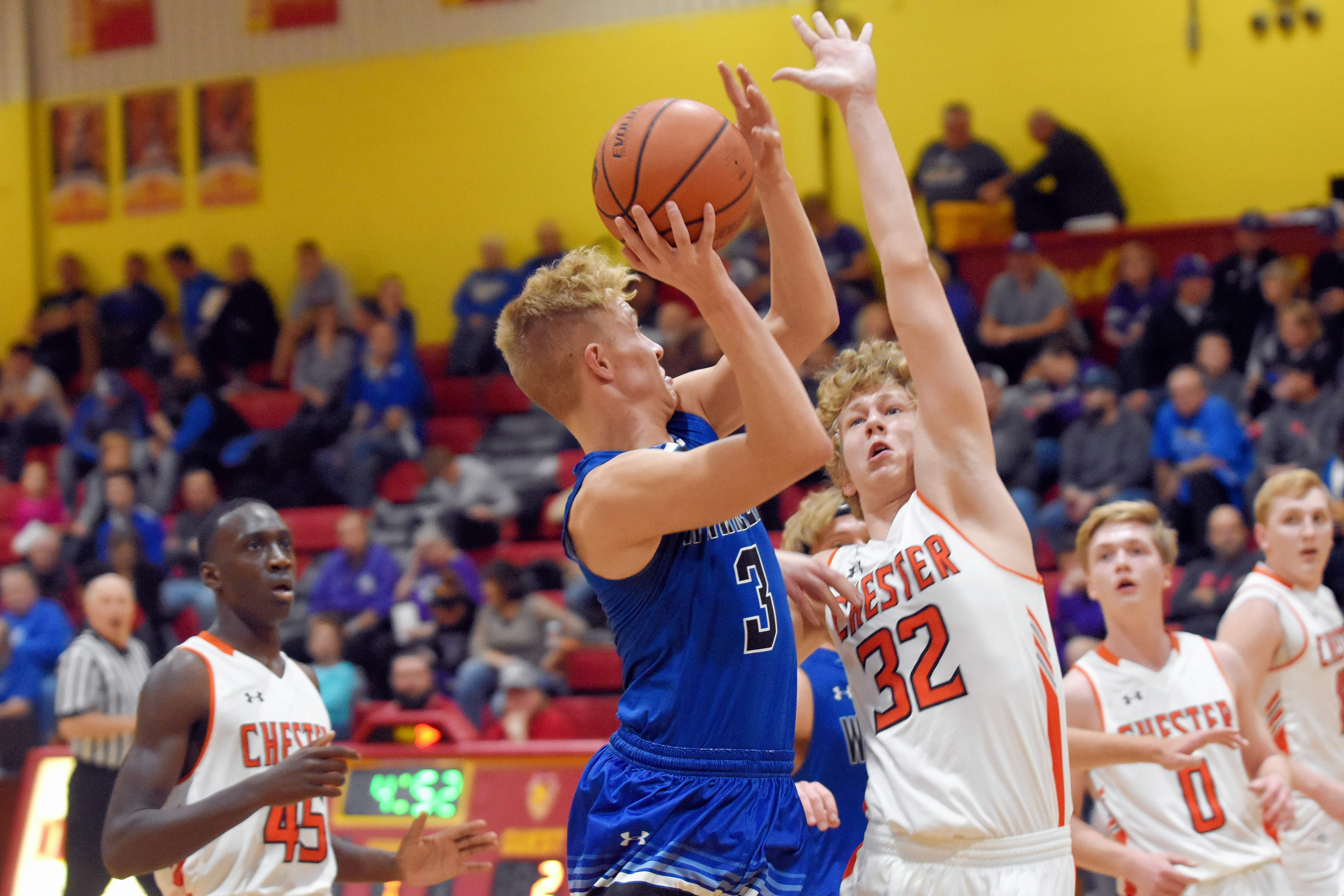 Steeleville's Owen Gross (left) looks to take a shot over Chester's Ian Reith (32). Gross led the Warriors with 28 points in Chester's 59-52 win.