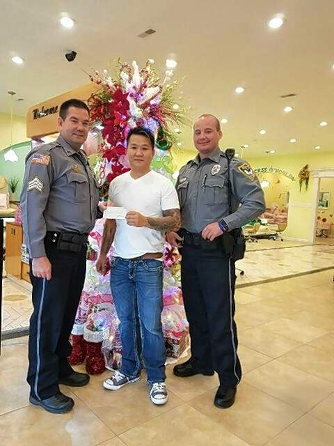 Harrisburg Police Department officers Michael Riden, left, and Eric Gott, right, receive a $200 donation from Sonny Nguyen, owner of Fancy Nails.