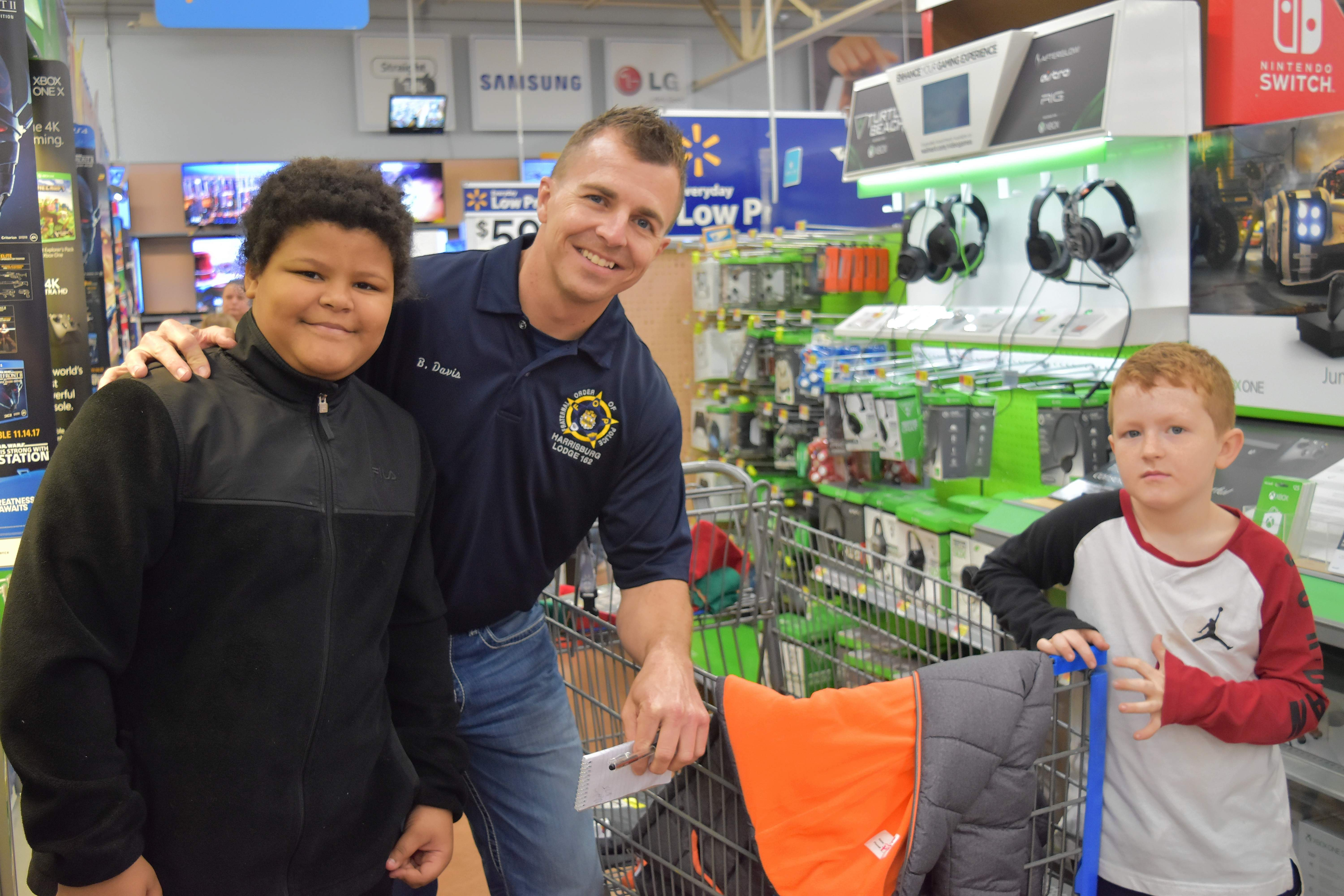 Harrisburg Police Department Officer Brent Davis shops with Zay Hortin, left, and Parker Miller at Shop With a Cop Saturday at Wal-Mart in Harrisburg.