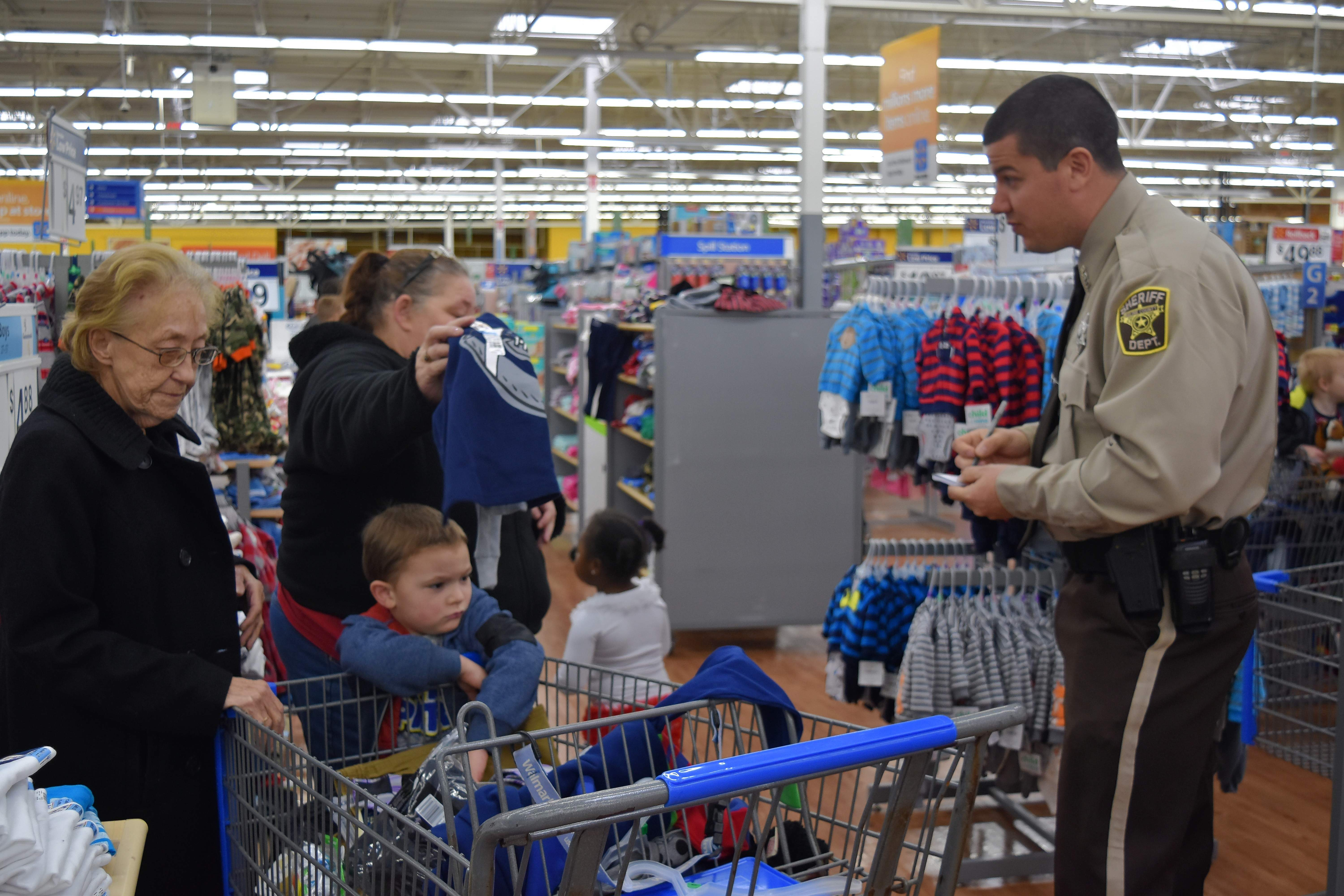 Saline County Deputy Craig Williams helps total a shopping list during Shop With a Cop Saturday at Wal-Mart in Harrisburg.