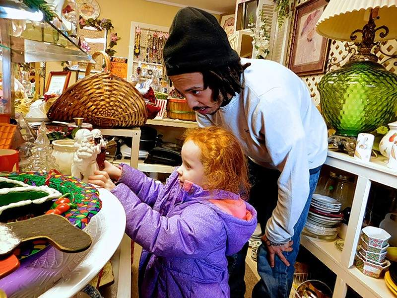 """Victoria Keeling, 4. and her stepfather, Dimitri Johnson, of Johnston City, look at some of the items at the thrift store. """"Everything in here is affordable,"""" he said. """"It's a good place to be."""""""