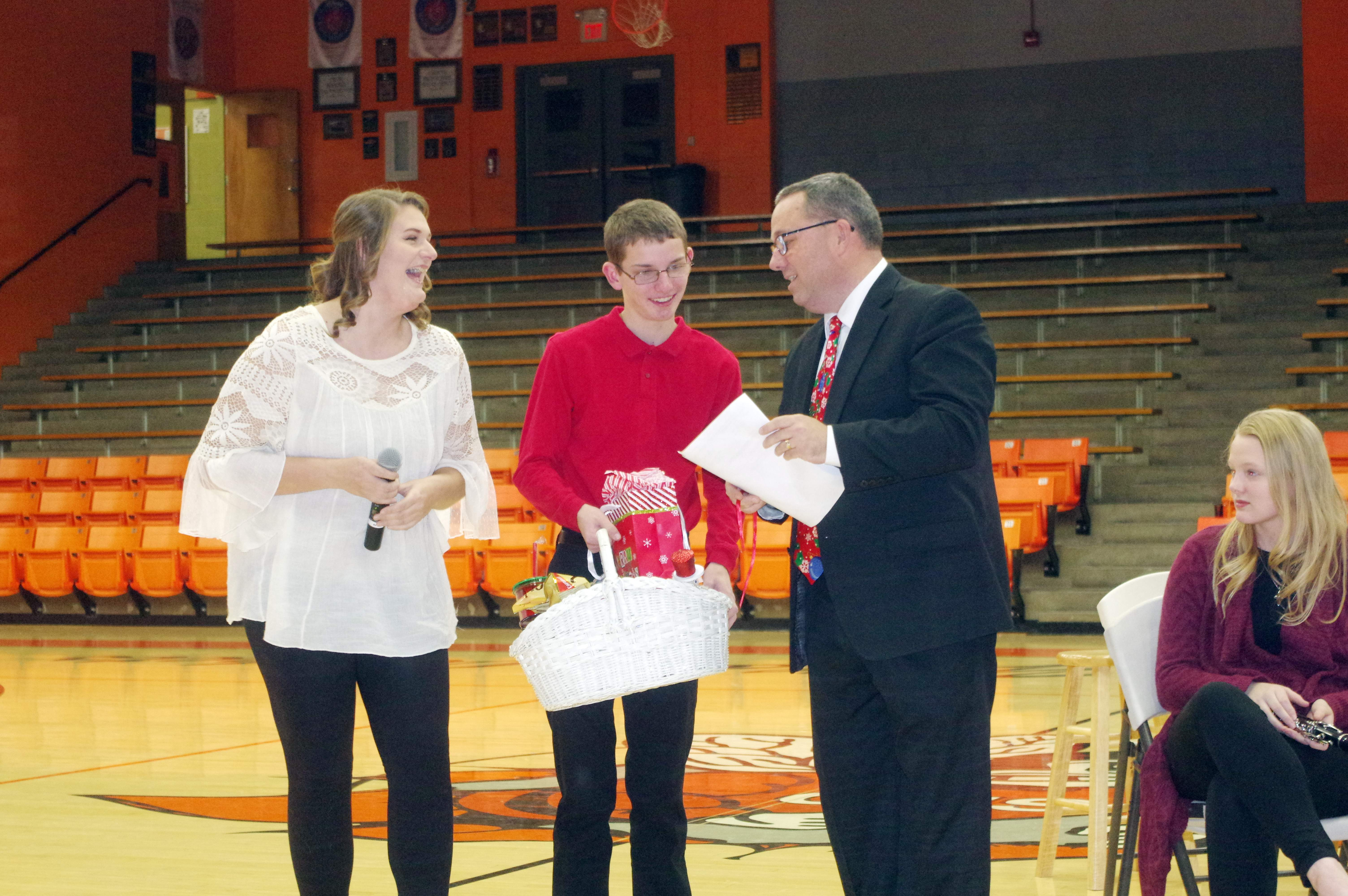Chester High School senior music students Montana Rose (left) and Mitchell Colonel present CHS Music Director Steve Colonel with a gift basket.