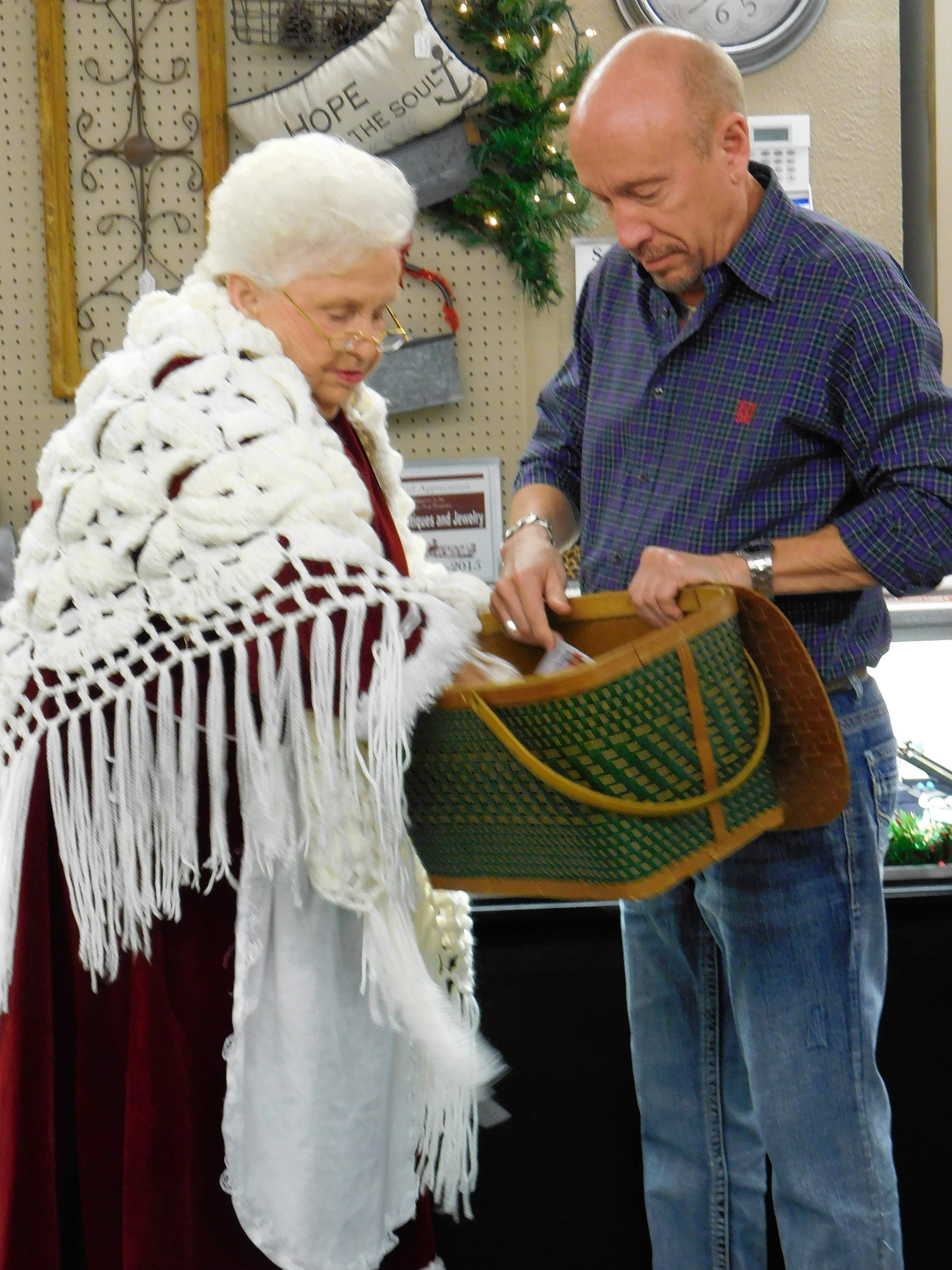 Mrs. Claus (Opal Avery of Johnston City) helped Kevin Edwards draw the raffle winners after an evening of posting for photos courtesy of Shooting Star Photography. Edwards raffled five items donated by the family of the late Robert and Georgina Hill.