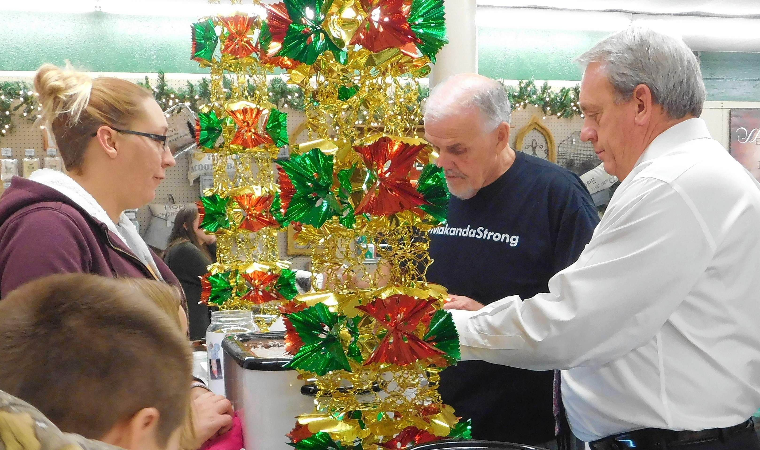 Sarah Carlton (left) speaks with Franklin County Circuit Clerk Jim Muir and Sen. Dale Fowler (R-Harrisburg) Friday evening during the Miracle for Makanda event at Edwards Antiques. The event was held to support Carlton's daughter, Makanda Williams, to aid in funding medical treatment for a rare brain tumor. Fowler and Muir volunteered to serve hot chocolate and cider during the event.